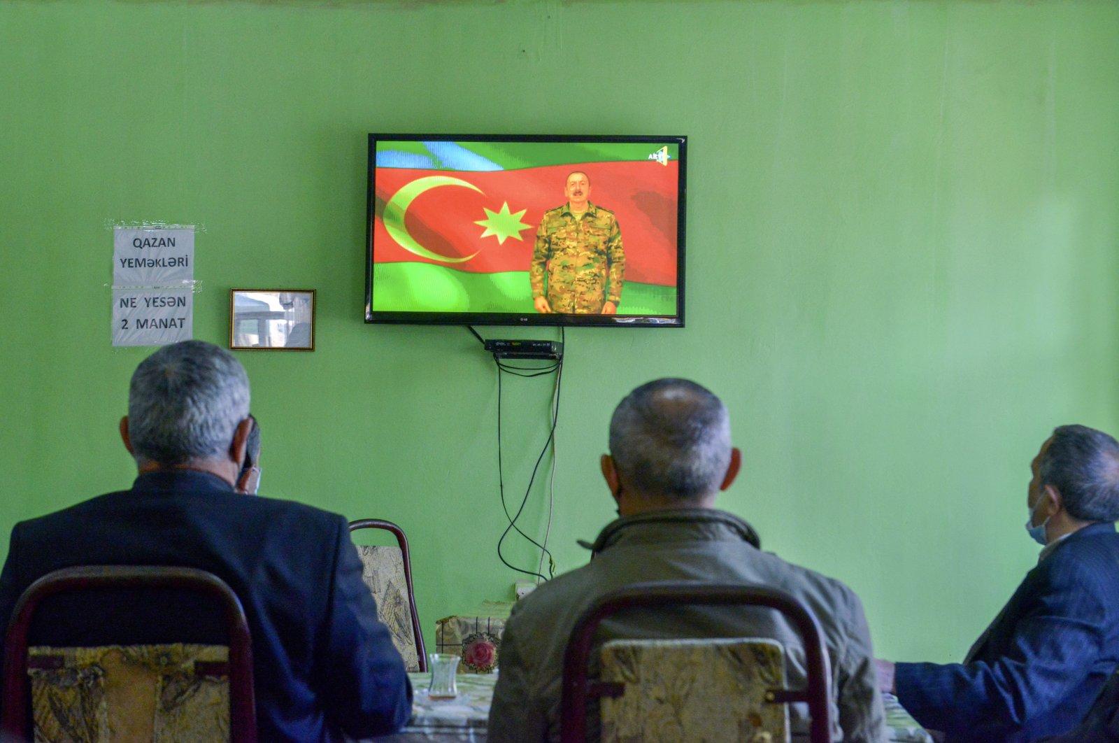 People listen to Azerbaijan's President Ilham Aliyev speaking on a television at a teahouse in Barda, Azerbaijan, Nov. 8, 2020. (AP Photo)