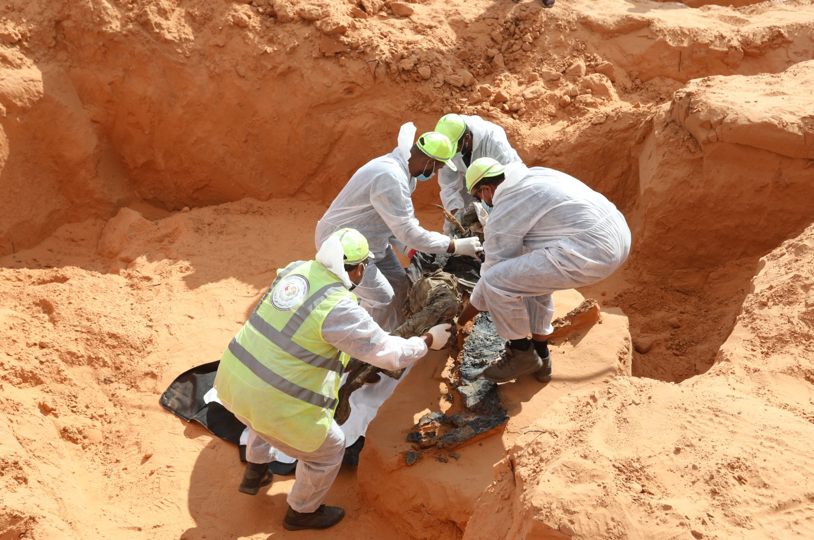 Libyan army personnel unearth corpses from a mass grave in Tarhuna, Nov. 9, 2020. (AA)