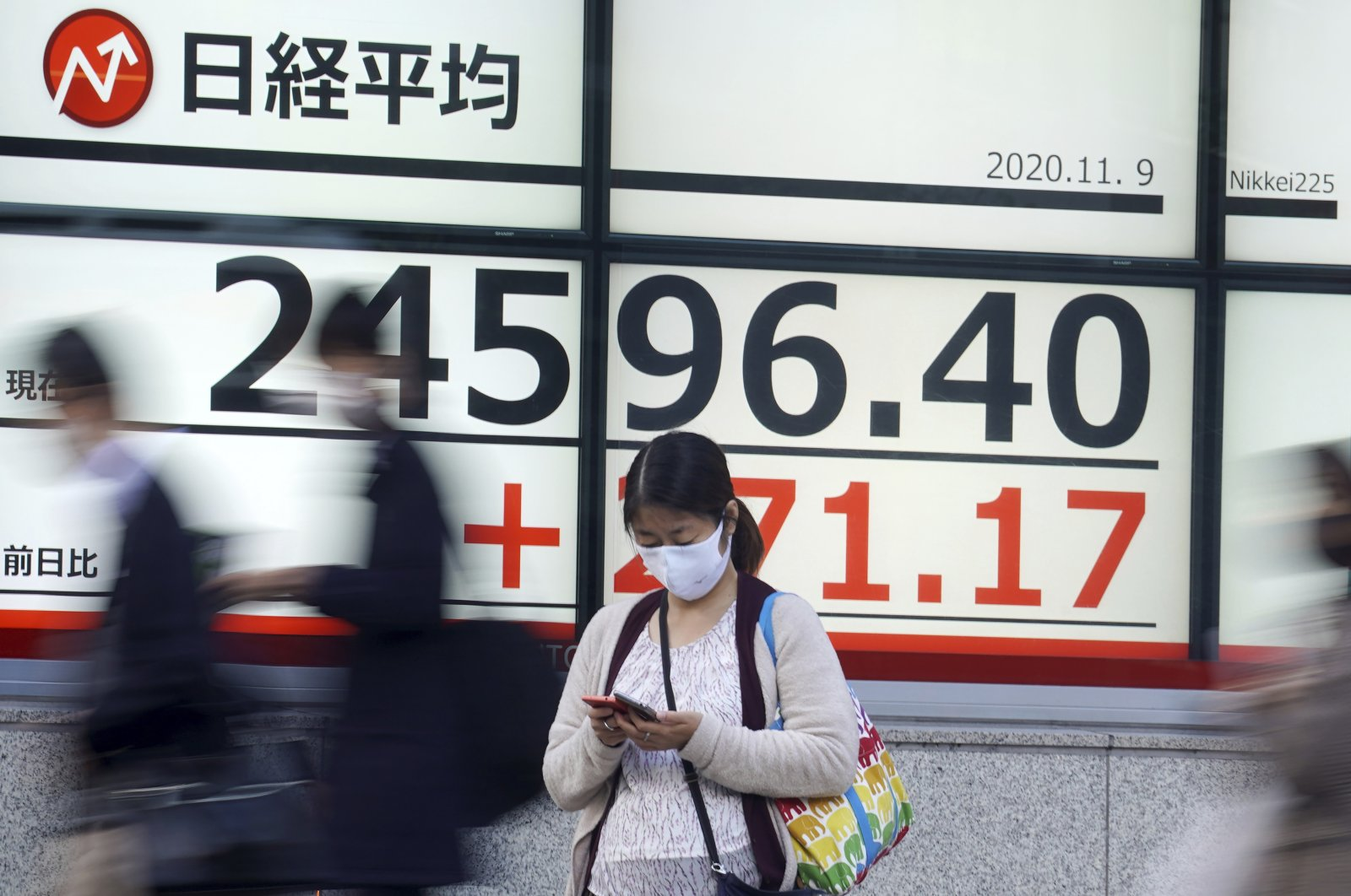A woman stands in front of an electronic stock board showing Japan's Nikkei 225 index at a securities firm in Tokyo, Nov. 9, 2020. (AP Photo)