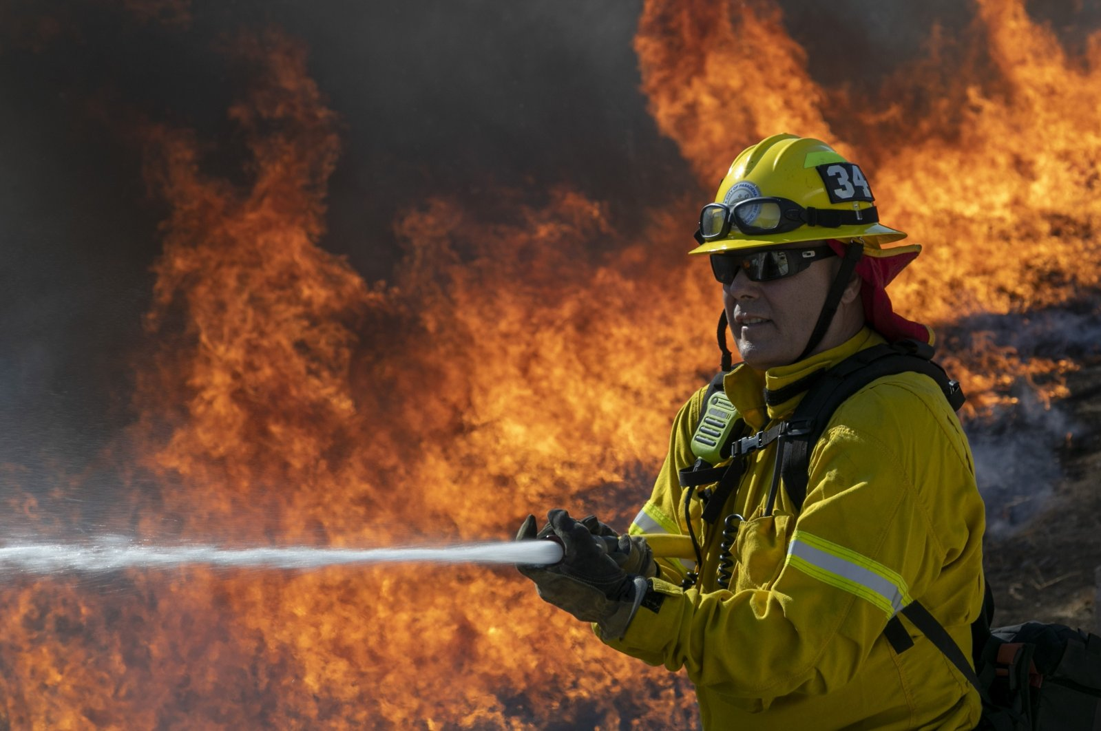 A firefighter protects a home from getting too hot as a backfire is set to protect homes and try to contain the Blue Ridge Fire on October 27, 2020 in Chino Hills, California. (AFP Photo)