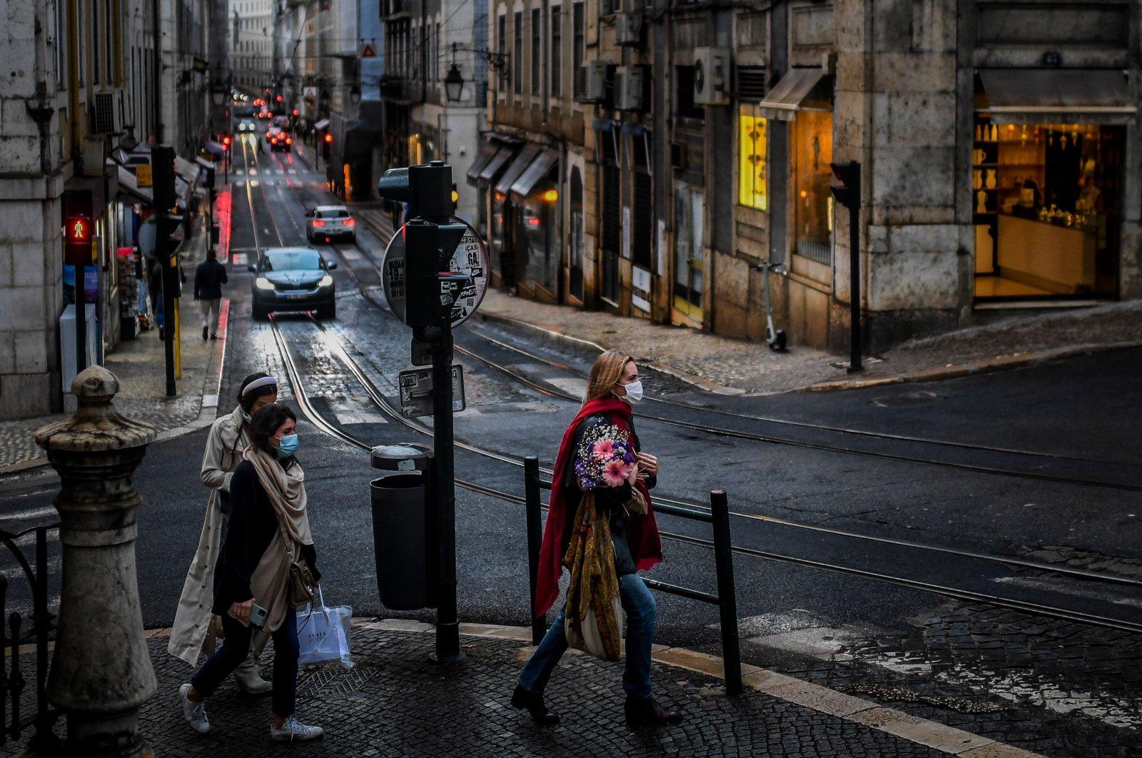 Women wearing masks cross a street in downtown Lisbon on Nov. 7, 2020. (AFP)