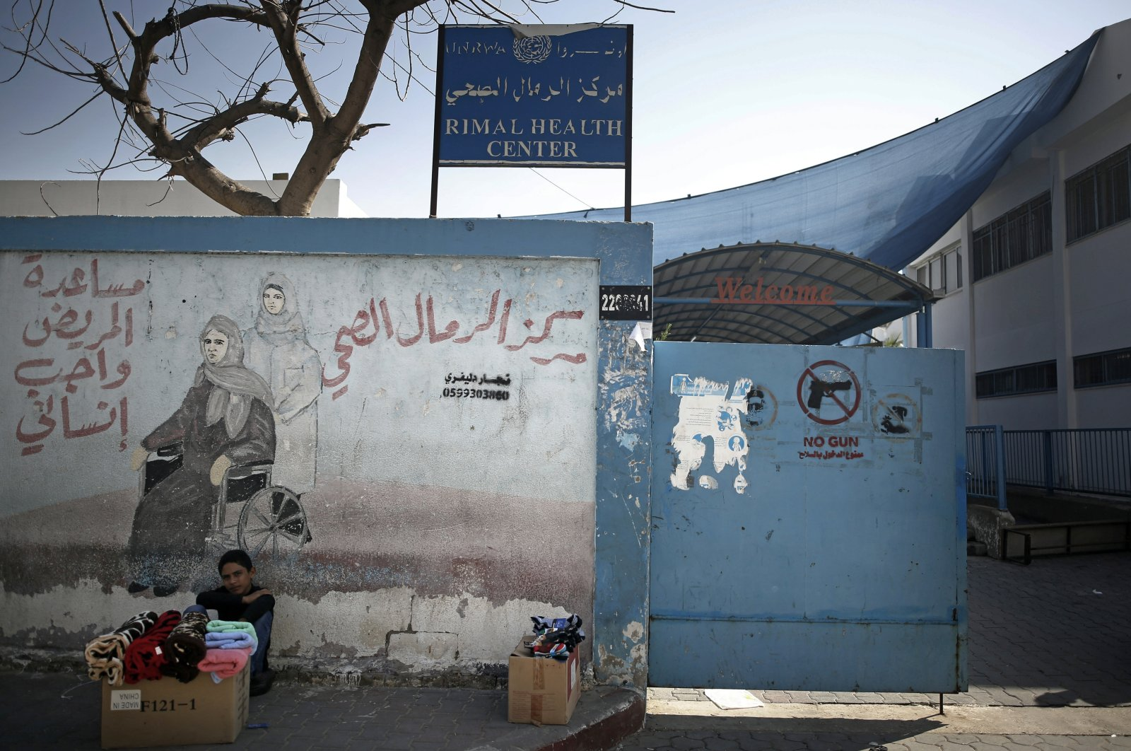 A Palestinian boy displays clothes for sale next to the entrance of the UNRWA Rimal Health Center, Gaza City, Nov. 9, 2020. (AP Photo)