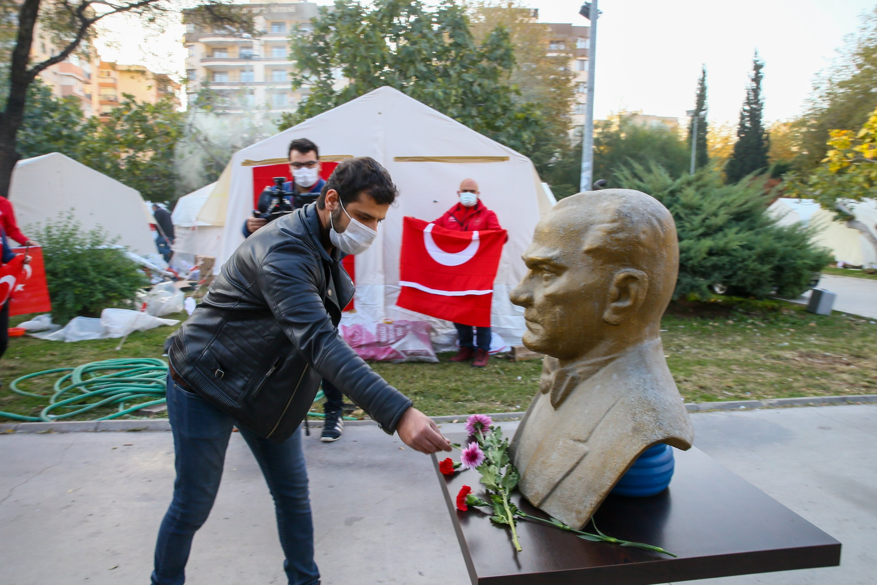 A man leaves flowers at a bust of Mustafa Kemal Atatürk next to tents set up for earthquake survivors in Izmir, western Turkey, Nov. 10, 2020. (AA Photo)
