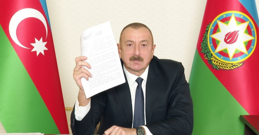 Azerbaijani President Ilham Aliyev holds a copy of the Nagorno-Karabakh peace deal during a televised address, Nov. 10, 2020. (AA Photo)