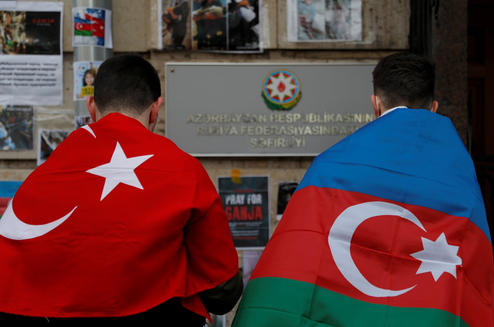Men holding the national flags of Azerbaijan and Turkey stand next to a makeshift memorial for people killed in Azerbaijan during the military conflict over the region of Nagorno-Karabakh, outside the embassy of Azerbaijan in Moscow, Russia, Oct. 19, 2020. (Reuters Photo)