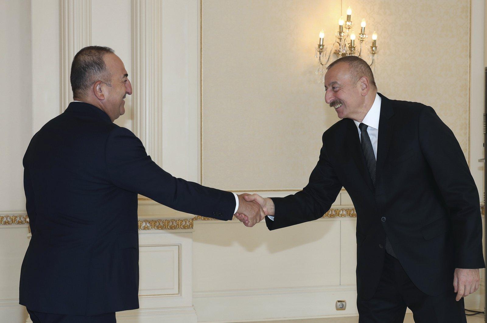 Azerbaijani President Ilham Aliyev (R) and Turkey's Foreign Minister Mevlüt Çavuşoğlu shake hands before a meeting, in Baku, Azerbaijan, Nov. 1, 2020. (AP Photo)