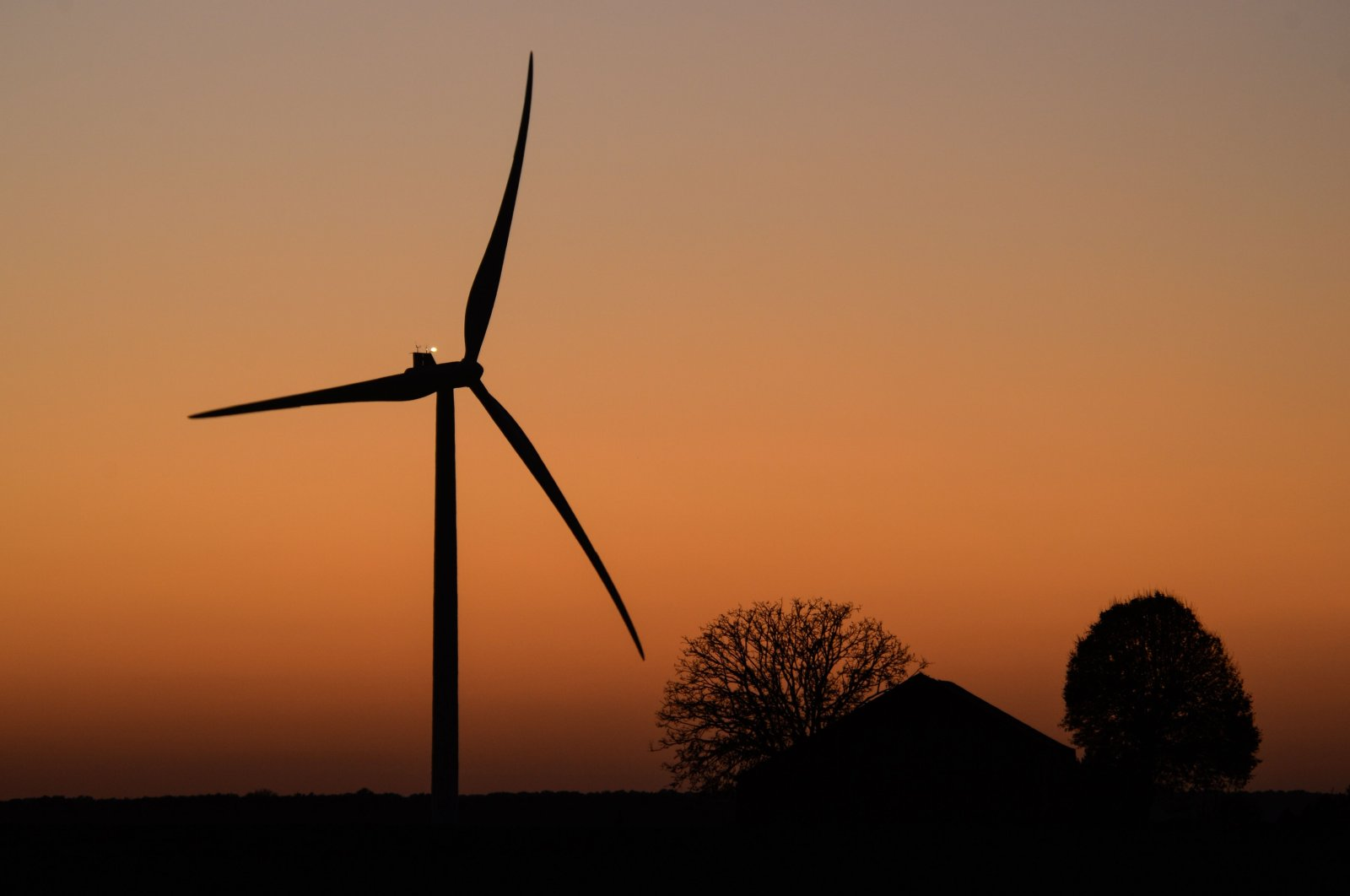A wind turbine is seen near an outcropping of trees as the sun sets on the Route de Magny near Illiers-Combray, central France, Nov. 5, 2020. (AFP Photo)