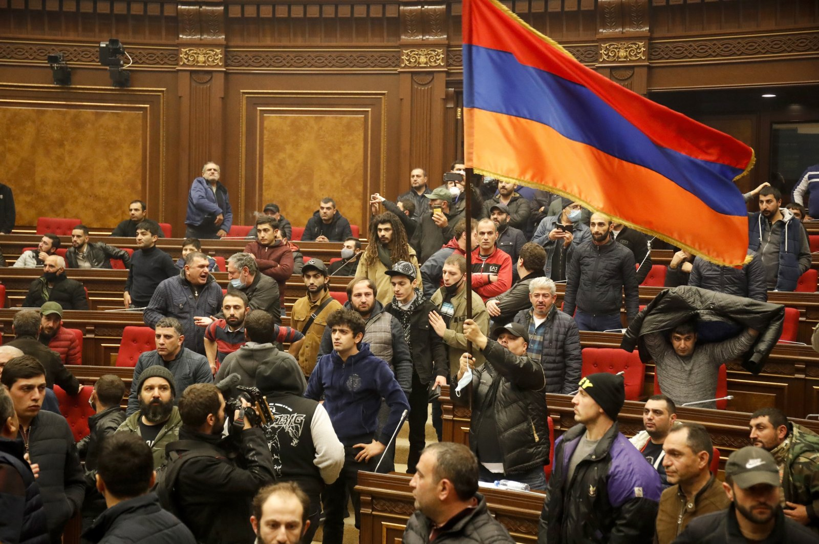 Demonstrators wave an Armenian flag in protest against a peace deal over the Nagorno-Karabakh region, at the national parliament building in Yerevan, Armenia, Tuesday, Nov. 10, 2020. (AP Photo)