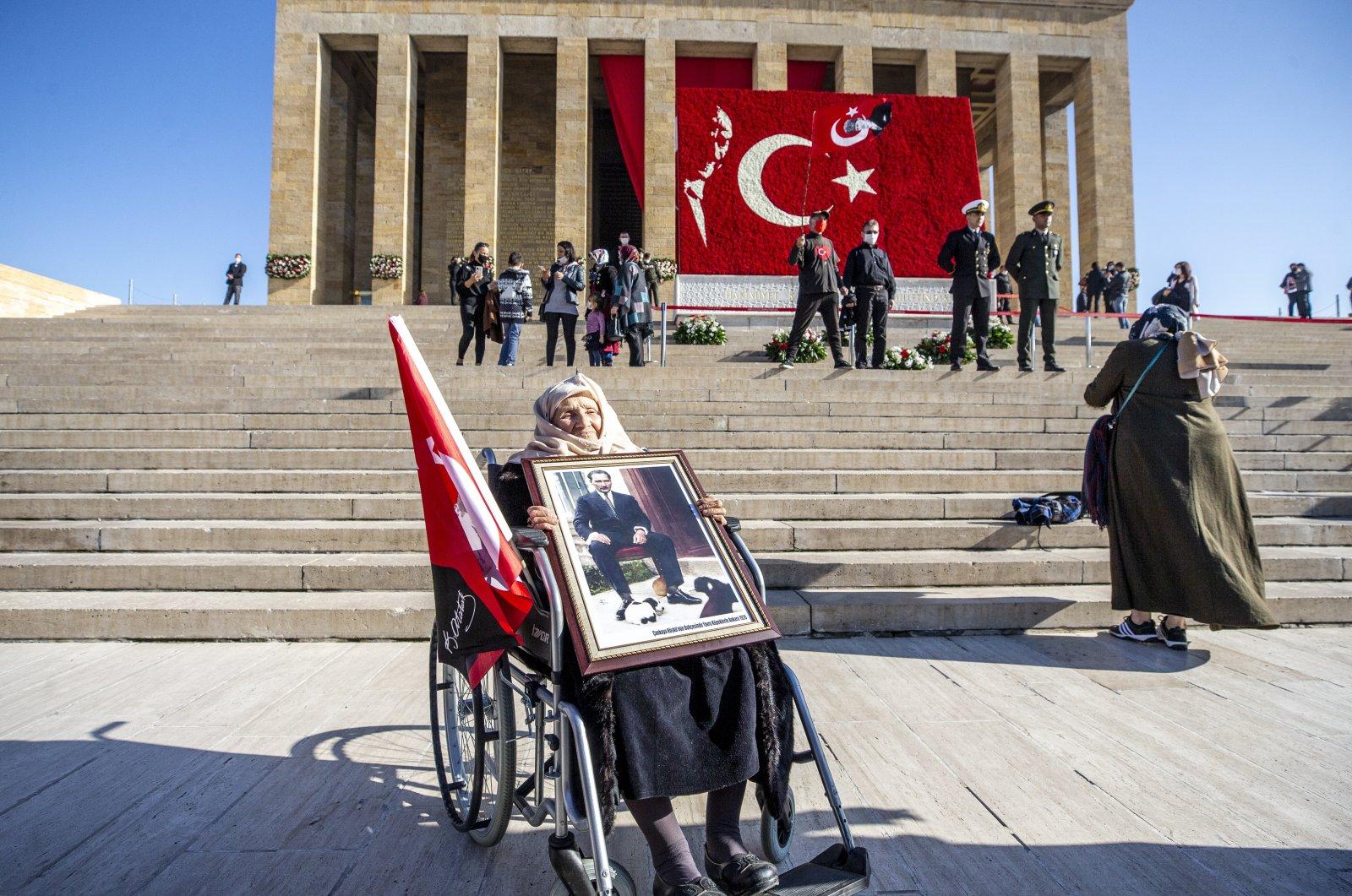 Gülten Gönen, 87, holds a portrait of Mustafa Kemal Atatürk outside his mauseloum Anıtkabir, in the capital Ankara, Turkey, Nov. 10, 2020. (AA Photo)