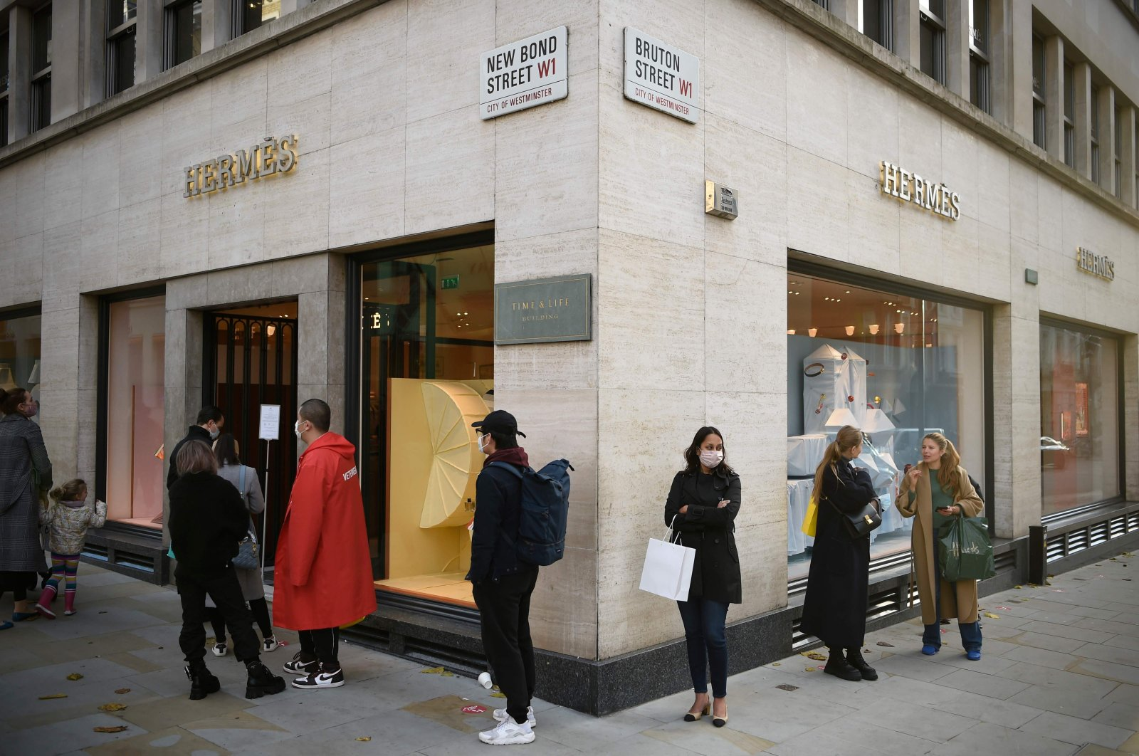 Shoppers queue to enter a branch of luxury fashion retailer Hermes in central London, Britain, Nov. 3, 2020 (AFP Photo)