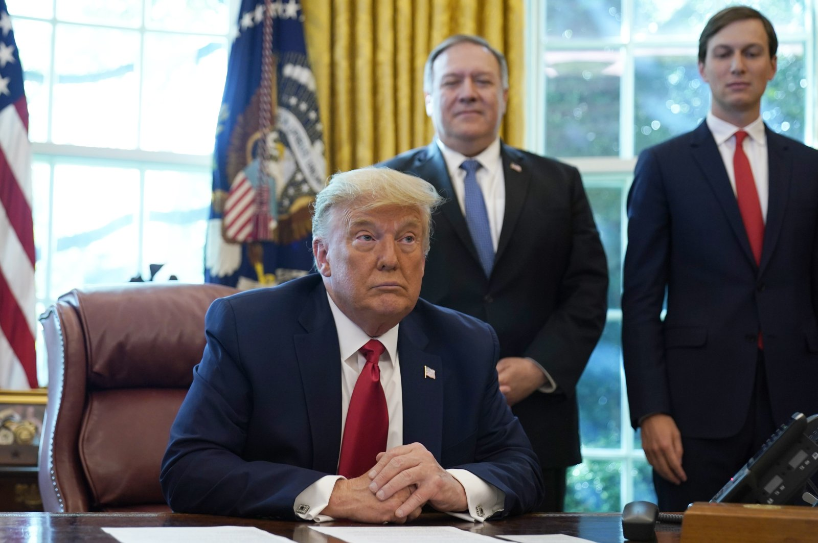 President Donald Trump listens while on a phone call with leaders of Sudan and Israel in the Oval Office of the White House, Washington, D.C., Oct. 23, 2020. (AP Photo)