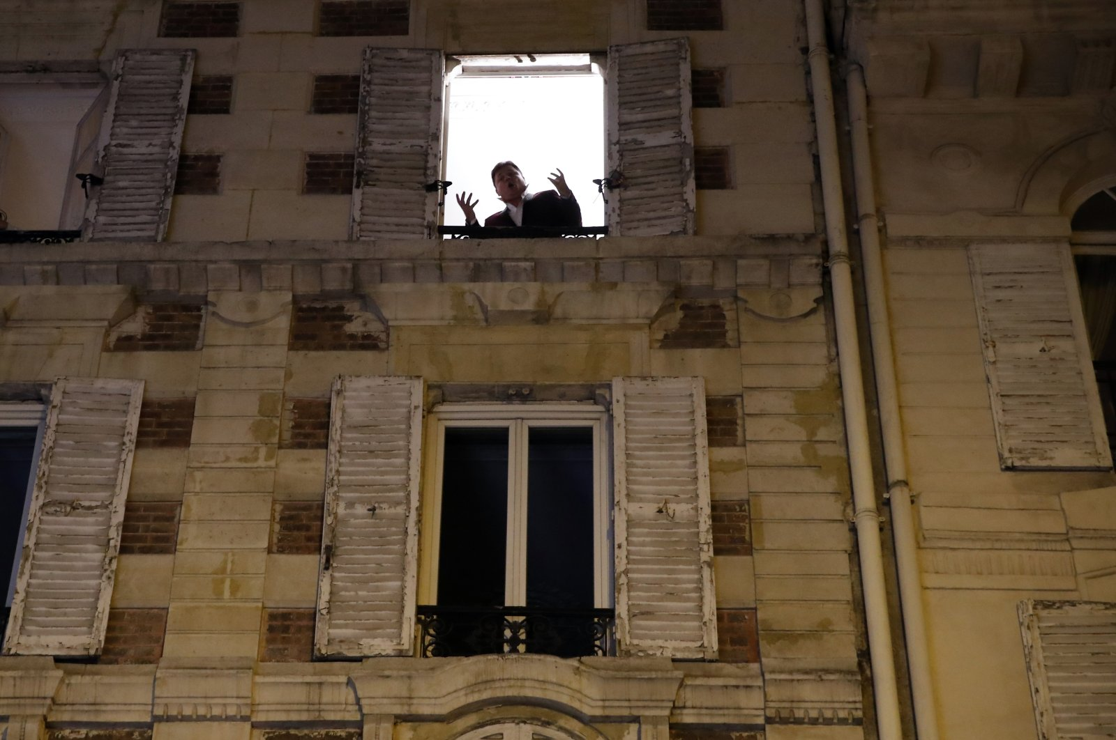 French tenor singer Stephane Senechal sings at dusk, the U.S. national anthem and Tosca of Puccini, from his apartment window during the monthlong partial lockdown to stop fast-rising virus hospitalizations and deaths, in Paris, Monday, Nov. 09, 2020. (AP Photo)