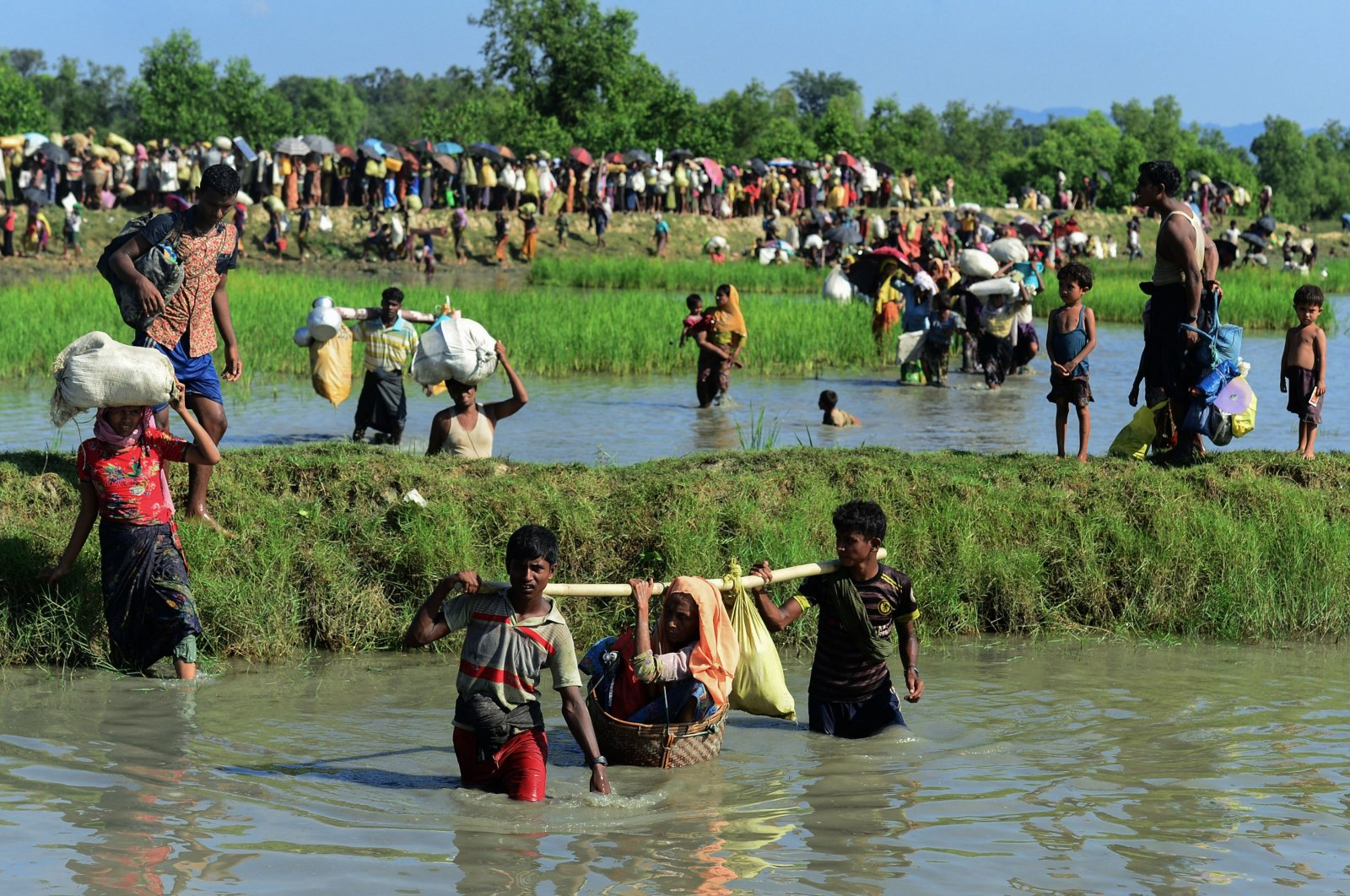 Rohingya refugees carry a woman over a shallow canal after crossing the Naf River as they flee violence in Myanmar to reach Bangladesh in Palongkhali near Ukhia, Oct. 16, 2017. (AFP Photo)