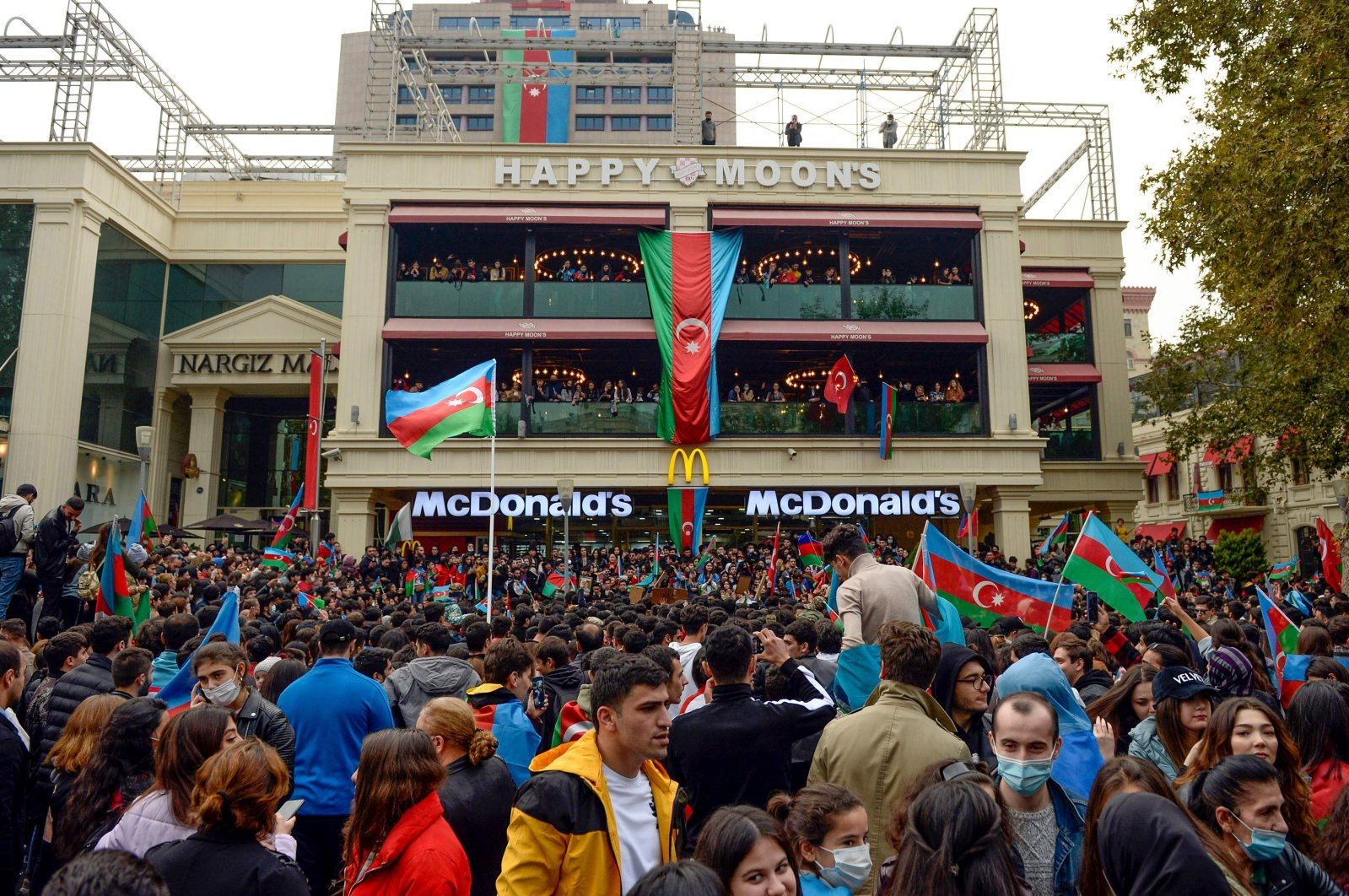Azerbaijanis wave the national flag as they celebrate in the streets of the capital Baku, Nov. 10, 2020. (AFP Photo)
