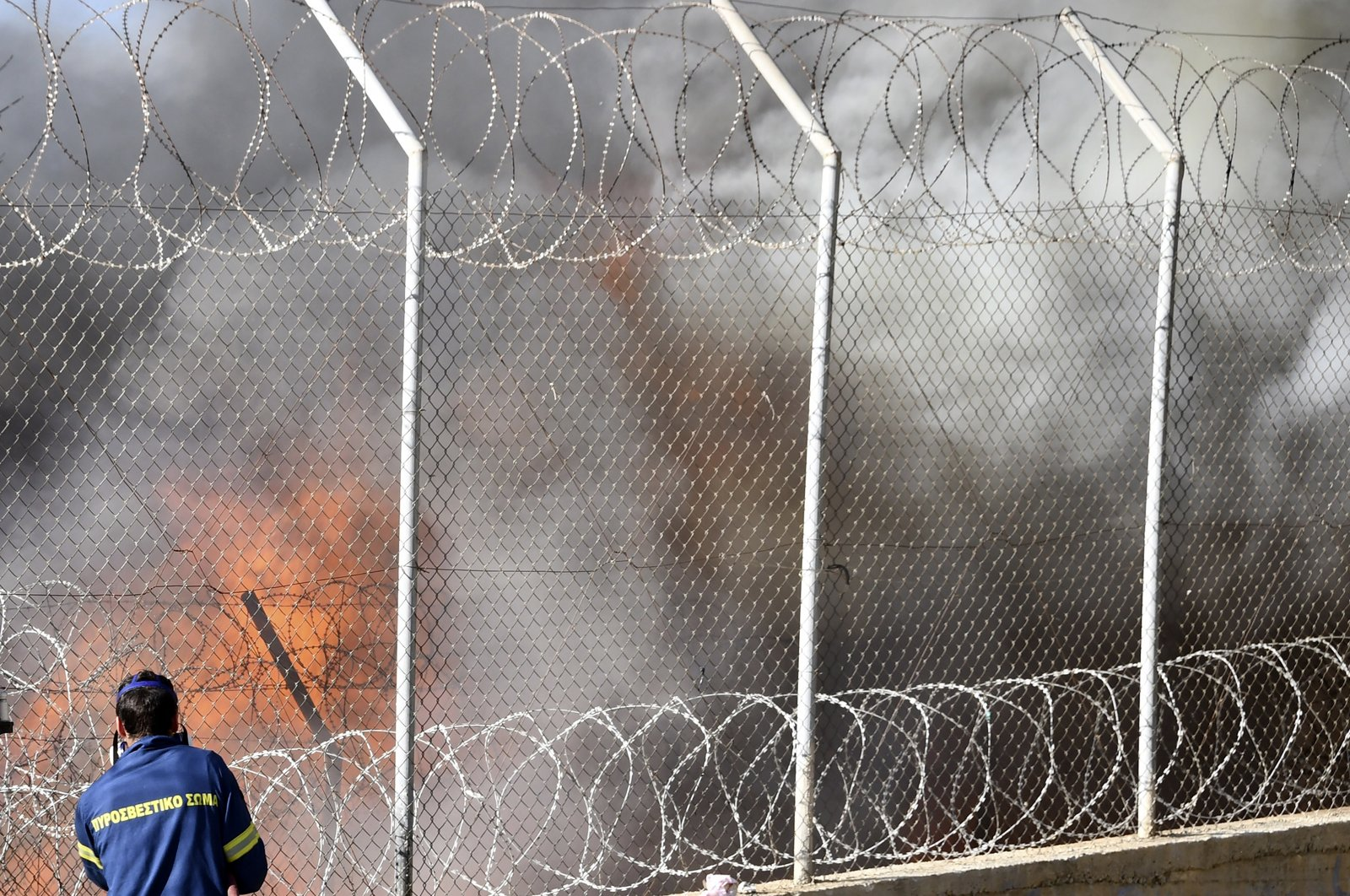A firefighter tries to extinguish a fire inside a refugee camp on the eastern Aegean island of Samos, Greece, Nov. 11, 2020. (AP Photo)