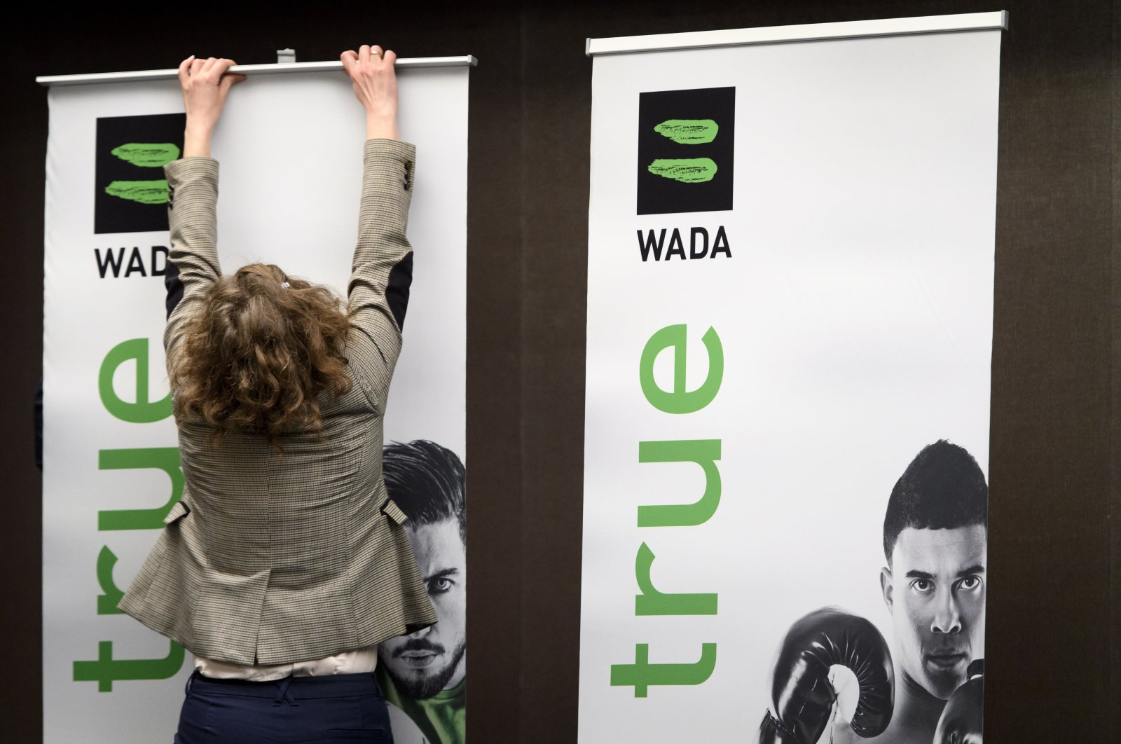 A World Anti-Doping Agency (WADA) employee mounts a banner featuring the WADA logo, at a press conference in Lausanne, Switzerland, Dec. 9, 2019. (EPA Photo)