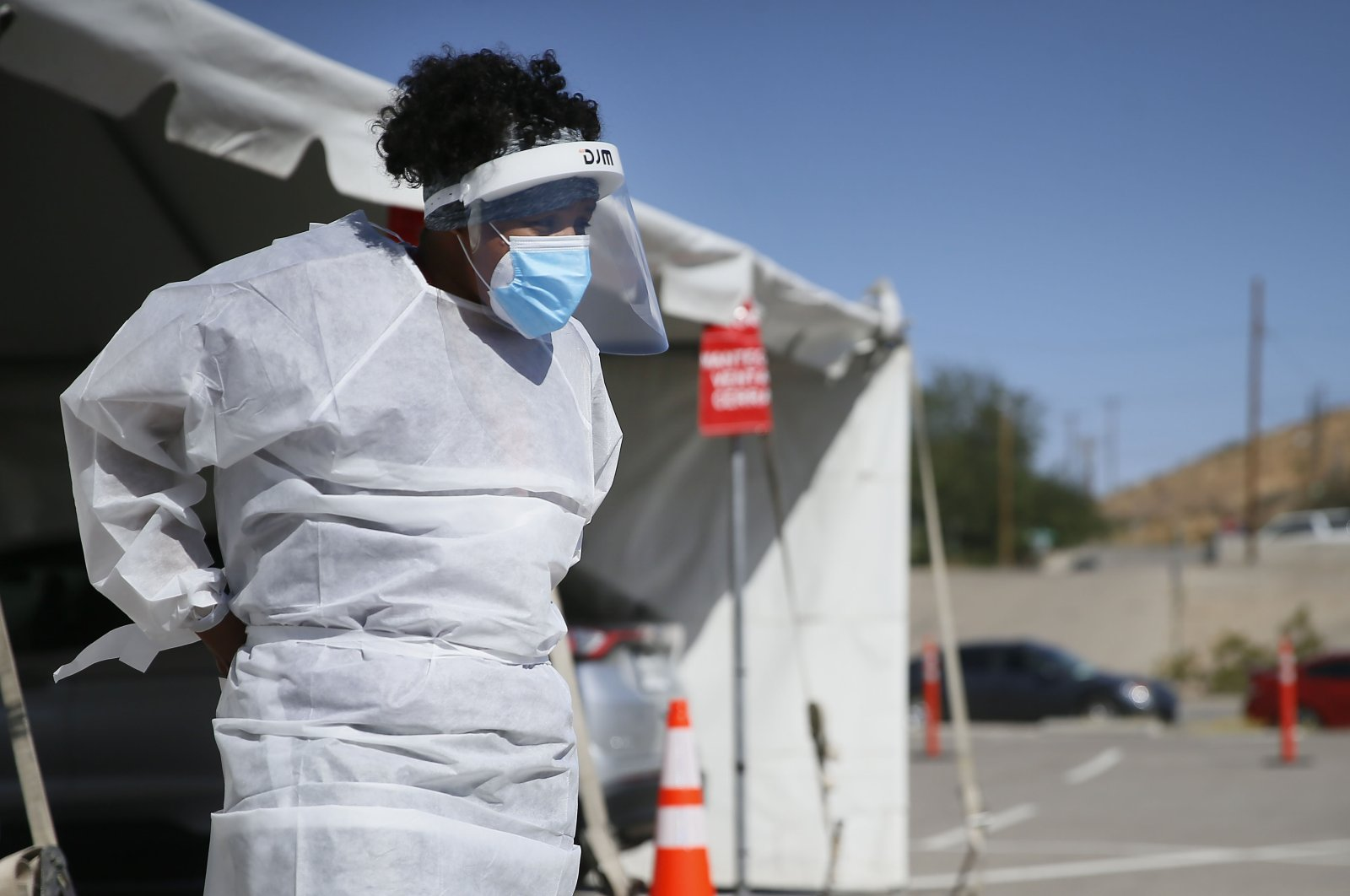 A medical worker stands at a COVID-19 state drive-thru testing site at UTEP, in El Paso, Texas, Oct. 26,2020. (The El Paso Times via AP)