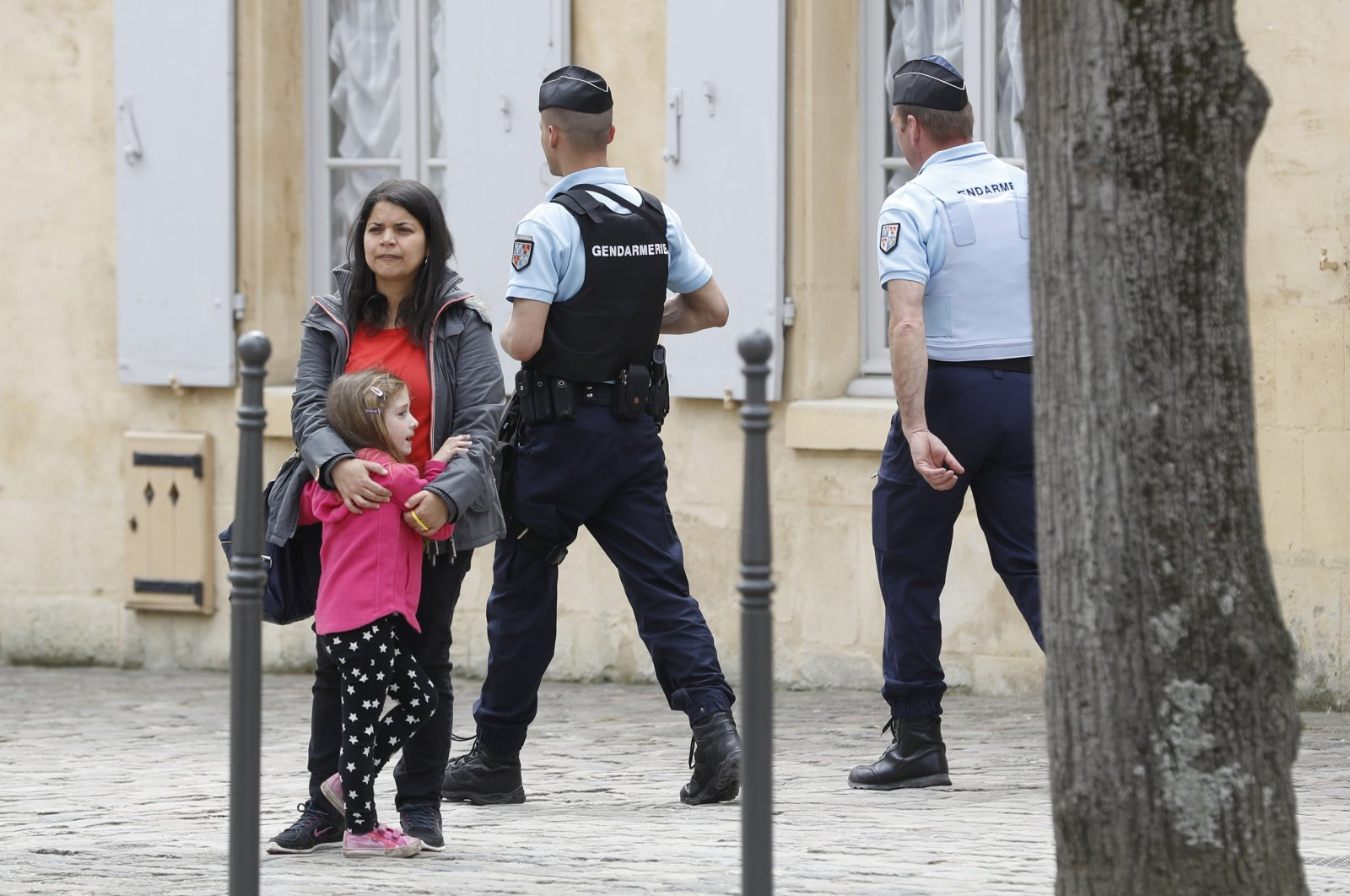 Police Officers patrol as a woman stands with a child in Chantilly, France in this undated picture. (Reuters Photo)