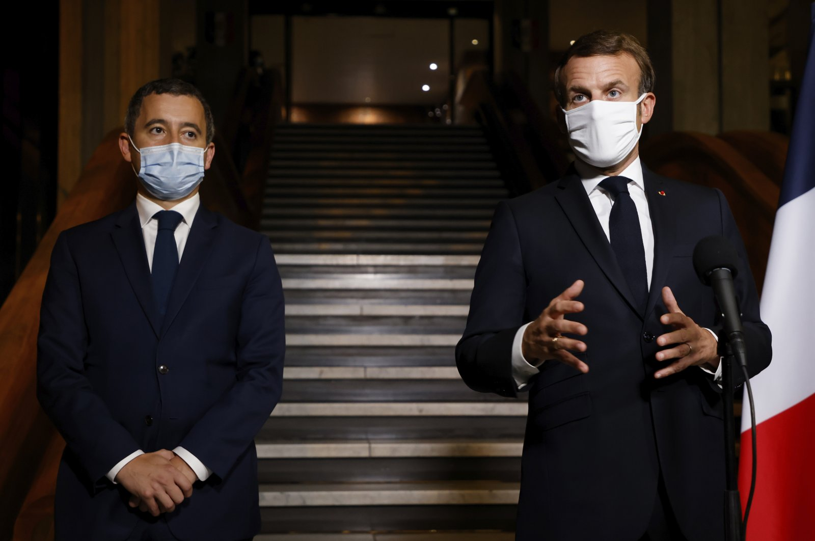 French President Emmanuel Macron (R) delivers a speech while Interior Minister Gerald Darmanin listens nearby, in Bobigny, a northeastern suburb of Paris, France, Oct. 20, 2020. (AP Photo)