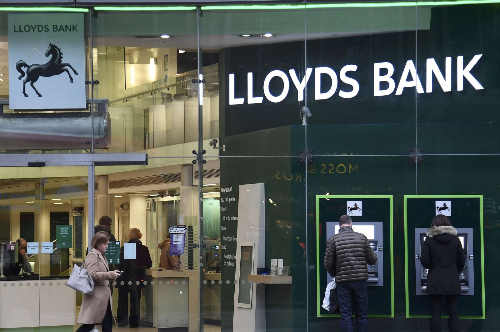 Customers use ATMs at a branch of Lloyds Bank in London, Feb. 21, 2017. (Reuters Photo)