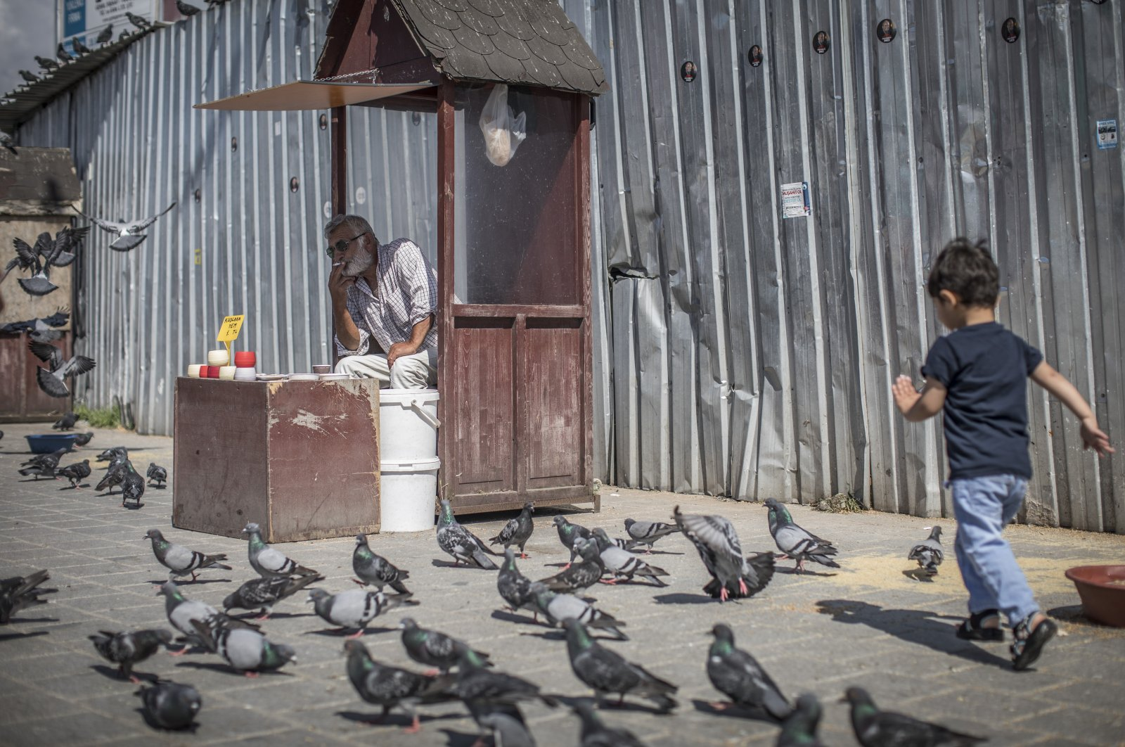 A vendor selling bird food smokes a cigarette as a boy chases pigeons in Istanbul, Turkey, 20 June 2018. (Getty Images)