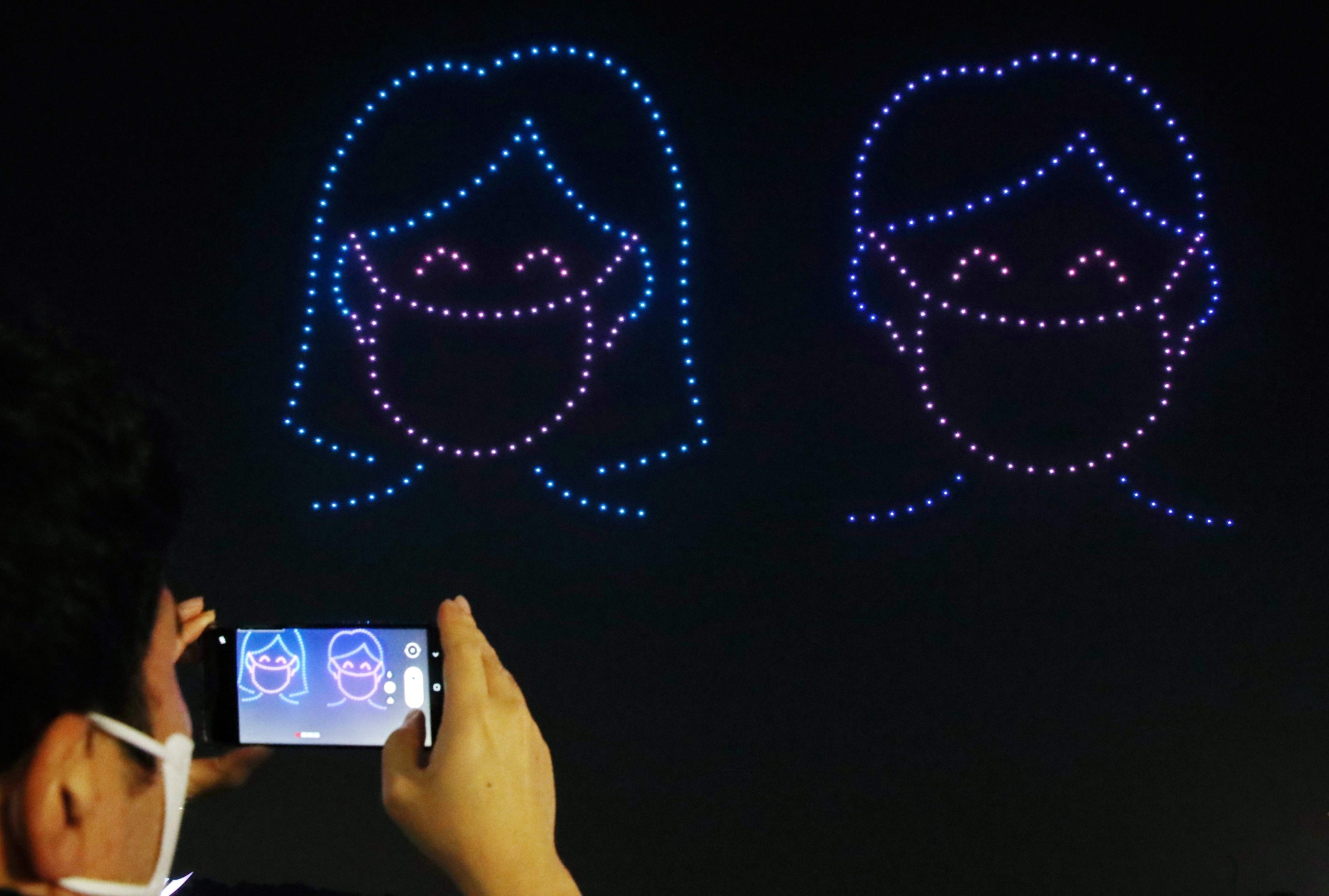 A spectator takes photos as 315 illuminated drones perform a routine to display messages and images of support for South Korea amid the coronavirus pandemic, Seoul, Nov. 13, 2020. (AFP Photo)