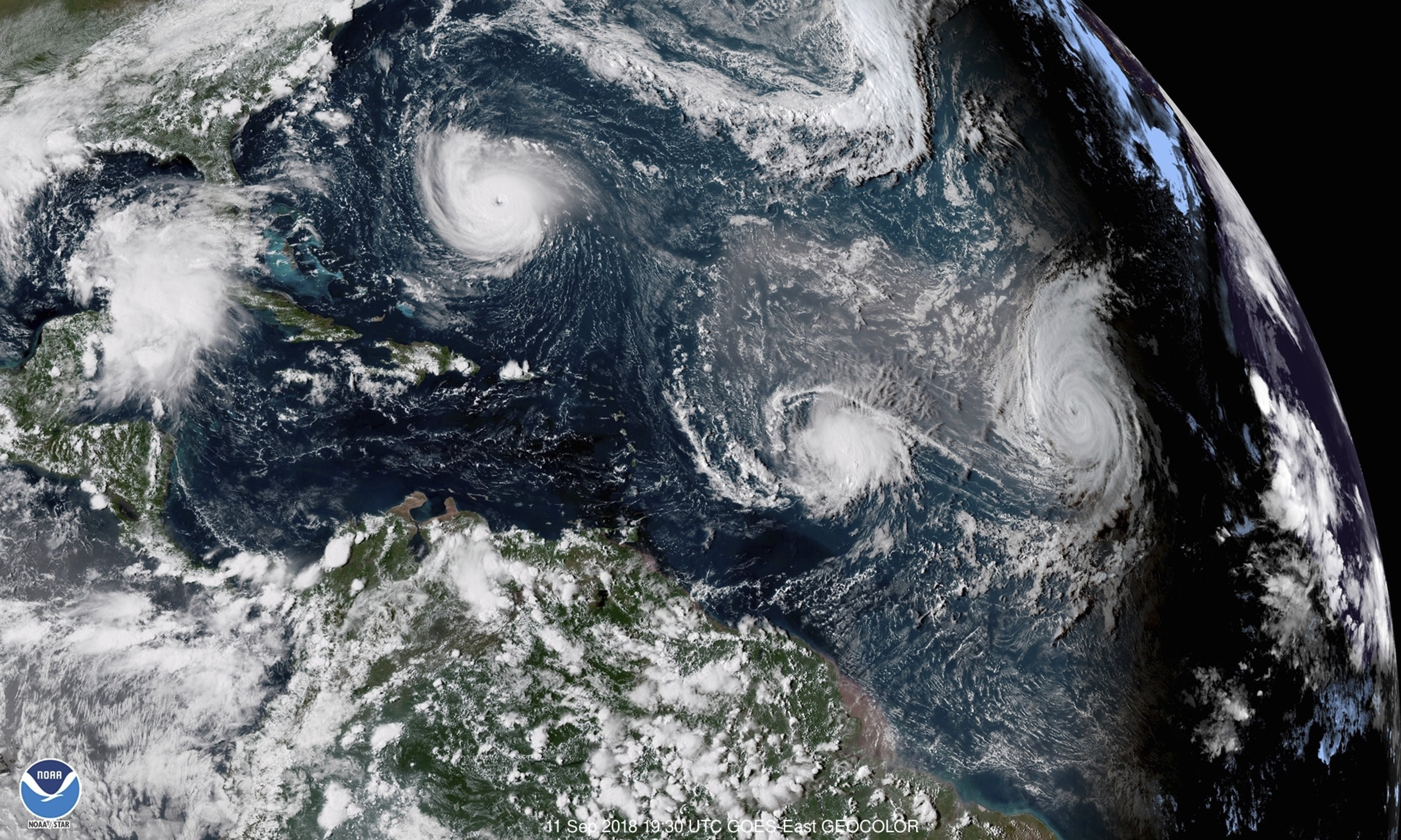 This enhanced satellite image made available by NOAA shows Tropical Storm Florence, upper left, in the Atlantic Ocean at 3:30 p.m. Eastern Standard Time, Sept. 11, 2018. (NOAA via AP)