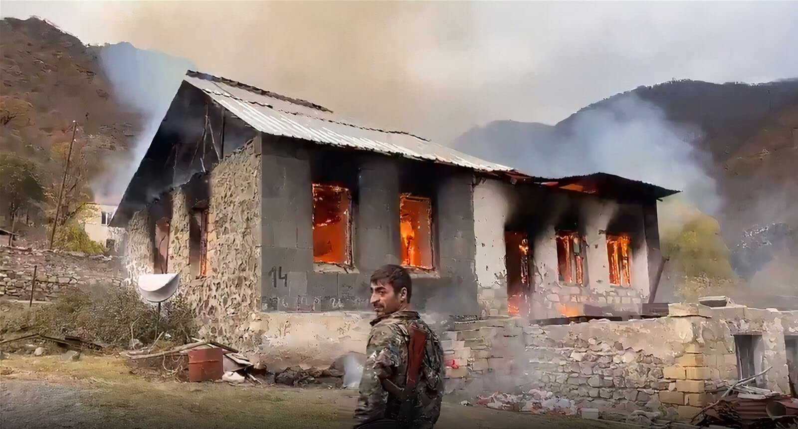 This image grab taken from a video broadcast on Russian media outlets shows a home burnt down by Armenians as they leave it before the arrival of Azerbaijani citizens in the Kalbajar area of Nagorno-Karabakh, Nov. 13, 2020.