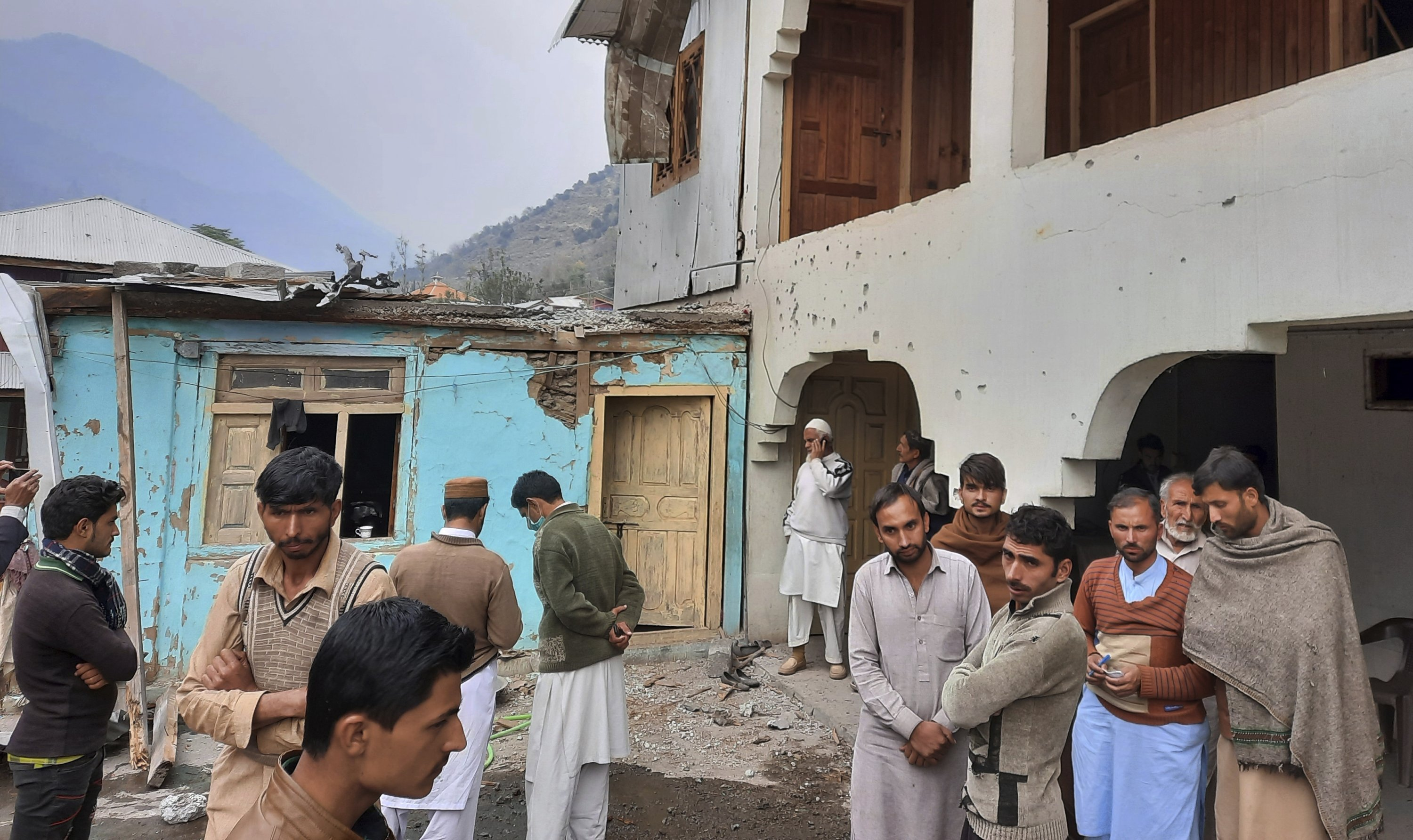 Local residents gather in a house damaged by shelling by Indian forces at a village in Neelum Valley, situated at the Line of Control (LoC) in Pakistan-administered Kashmir, Nov. 13, 2020. (AP Photo)