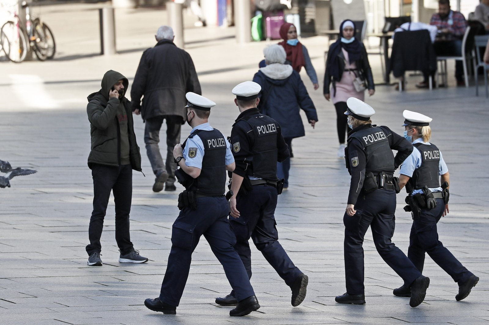 Police officers patrol in a street in Cologne, Germany, where masks are mandatory due to the coronavirus pandemic, Oct. 22, 2020. (AP Photo)