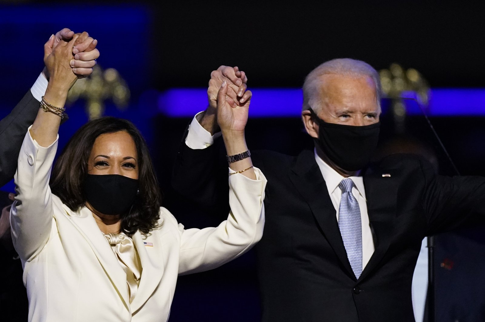 Vice President-elect Kamala Harris holds hands with President-elect Joe Biden and her husband Doug Emhoff as they celebrate in Wilmington, Delaware, Nov. 7, 2020. (AP Photo)