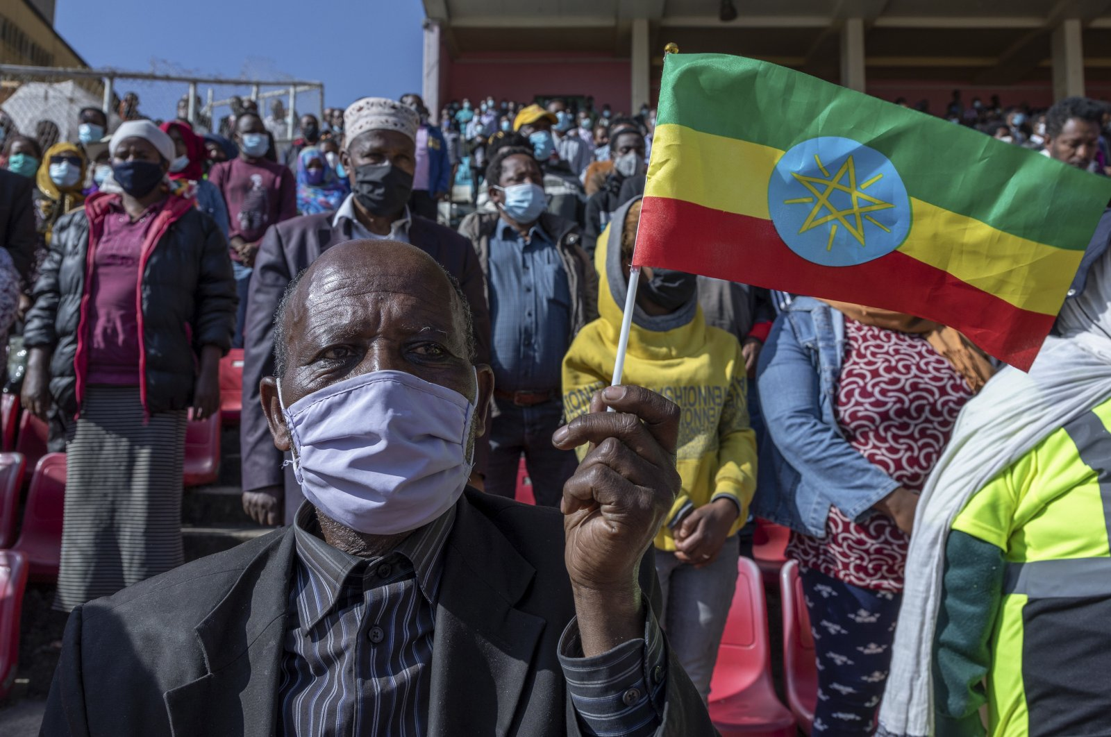 A man holds a national flag as he waits in the stands to give blood at a blood drive in support of the country's military, at a stadium in the capital Addis Ababa, Ethiopia, Nov. 12, 2020. (AP Photo)