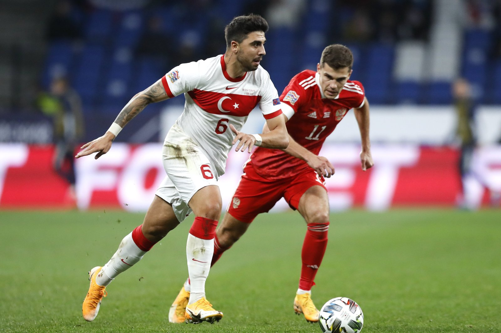 Turkey's Ozan Tufan (L) dribbles the ball past Russia's Roman Zobnin during a UEFA Nations League match, in Moscow, Russia, Oct. 11, 2020. (AP Photo)