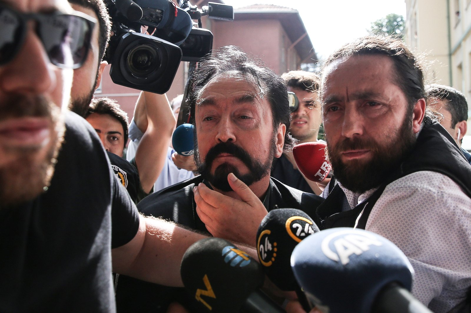Police escort Adnan Oktar to a hospital for a medical check before his detention, in Istanbul, Turkey, July 12, 2018. (AA Photo)