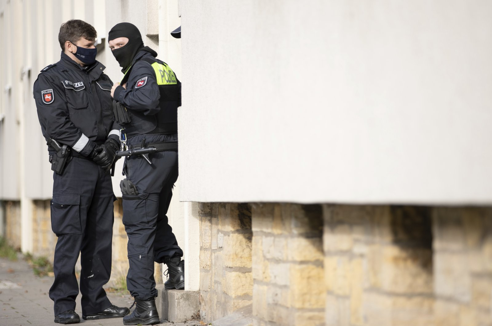 Police officers are standing outside an apartment building during a search in Osnabruck, Germany, Nov. 6, 2020. (AP Photo)
