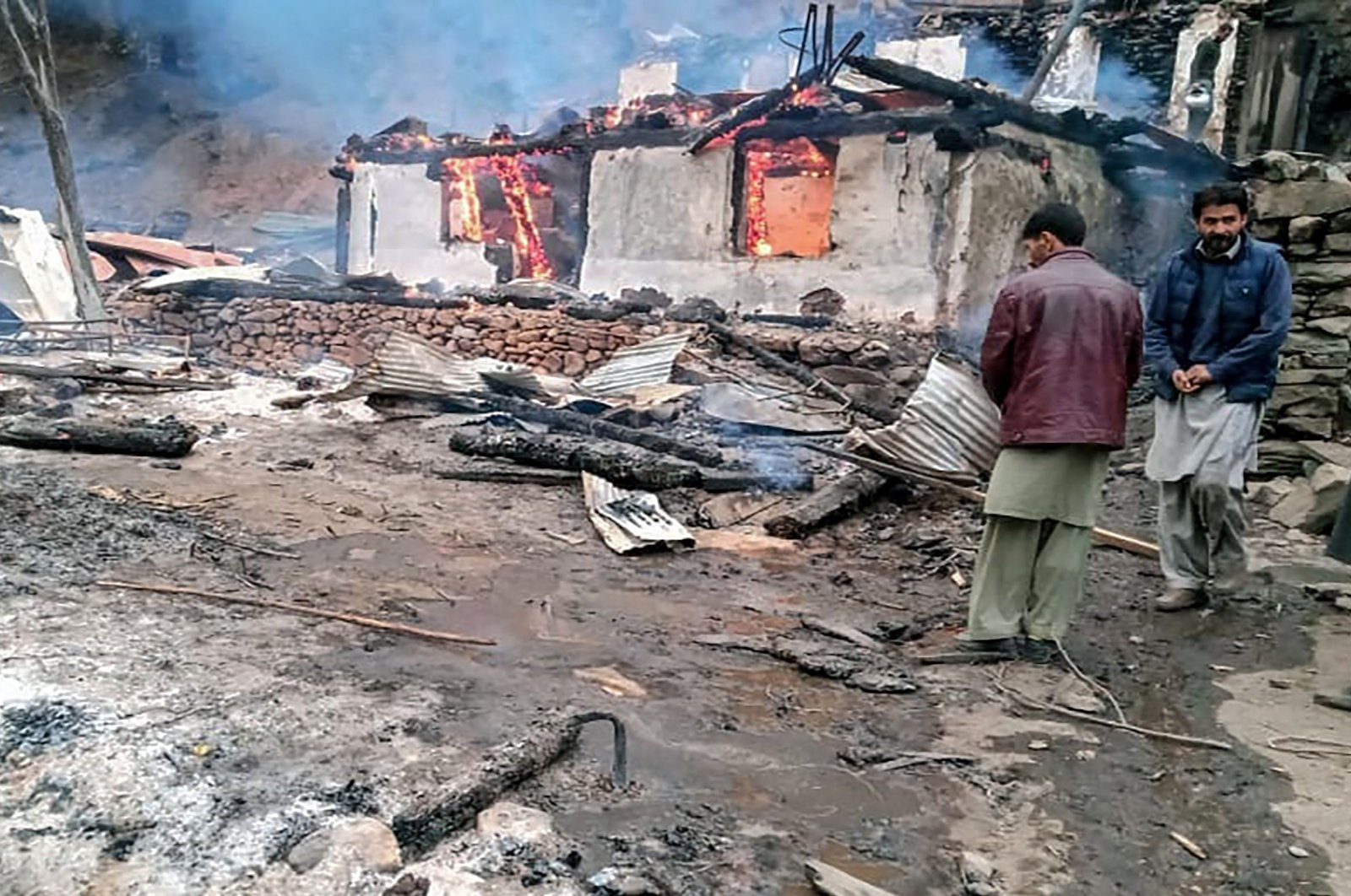 Local residents stand beside a burning house following cross-border shelling between Pakistani and Indian forces in the village of Tehjain at the Line of Control (LoC), the de facto border between Pakistan and India, in Neelum Valley of Pakistan-administered Kashmir, Nov. 13, 2020. (AFP Photo)