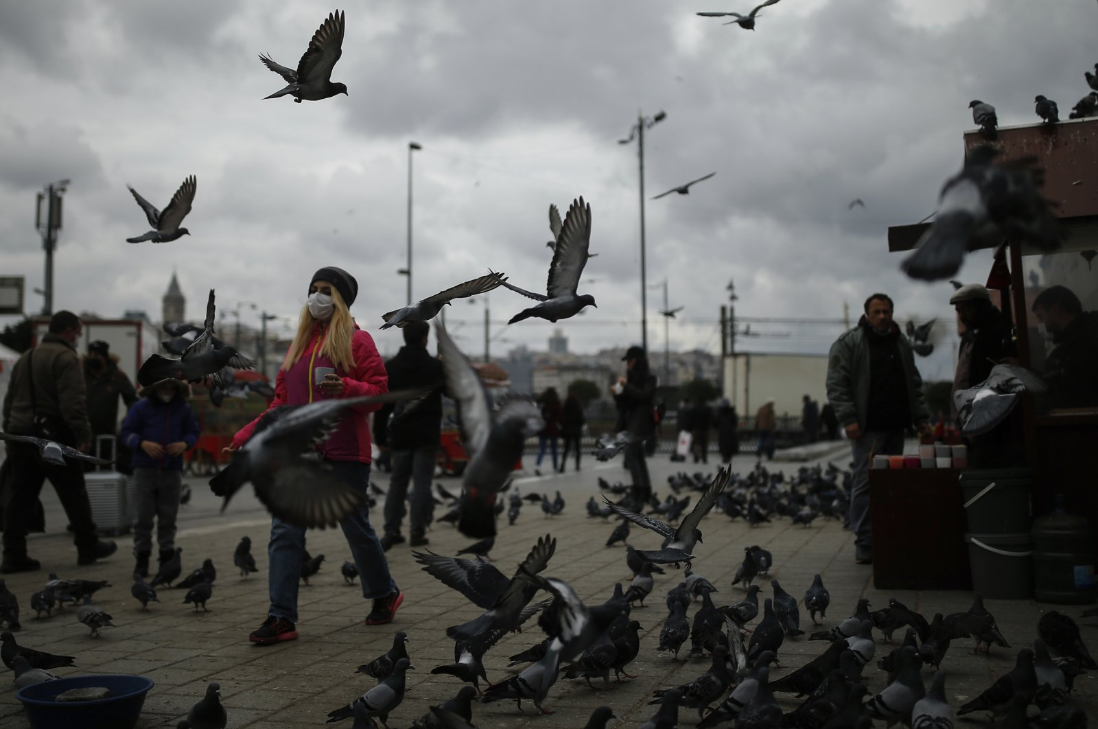 People, most wearing protective face masks to help protect against the spread of coronavirus, walk through the Eminonu Market by the Golden Horn in Istanbul, Nov. 10, 2020. (AP Photo)