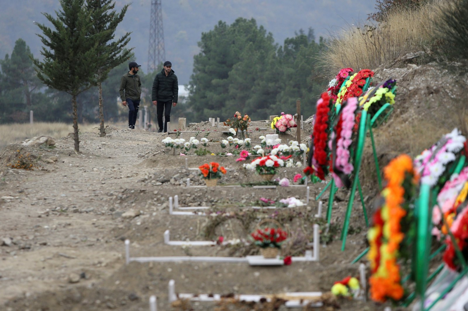 Men walk along graves of soldiers and civilians who were killed during clashes over Nagorno-Karabakh, in Stepanakert, Nov. 2, 2020. (Reuters Photo)
