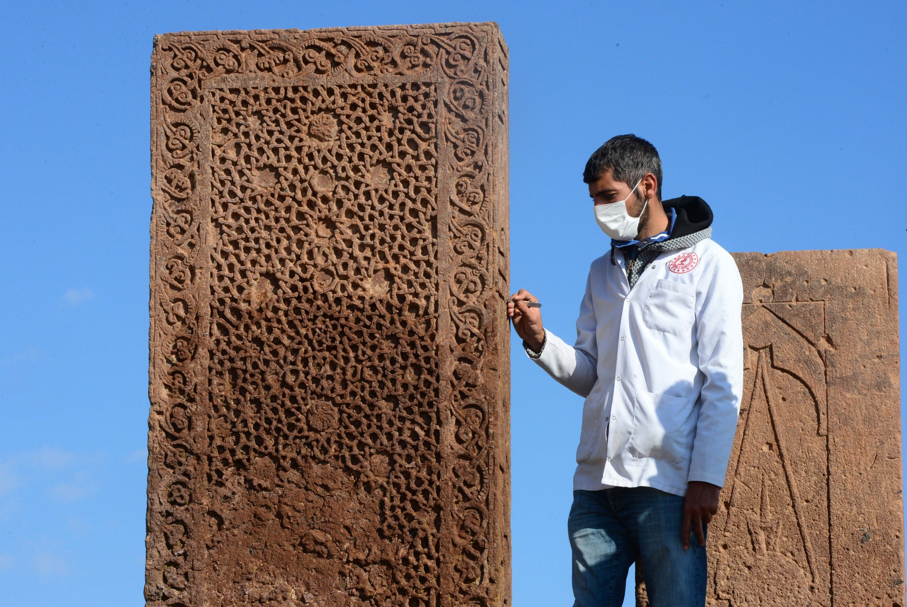 An archaeologist works on a tombstone in the Seljuk Meydan Cemetery, Bitlis, eastern Turkey, Nov. 12, 2020. (AA PHOTO)