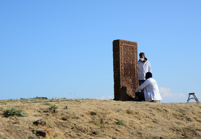 Two archaeologists work on a tombstone in the Seljuk Meydan Cemetery, Bitlis, eastern Turkey, Nov. 12, 2020. (AA PHOTO)