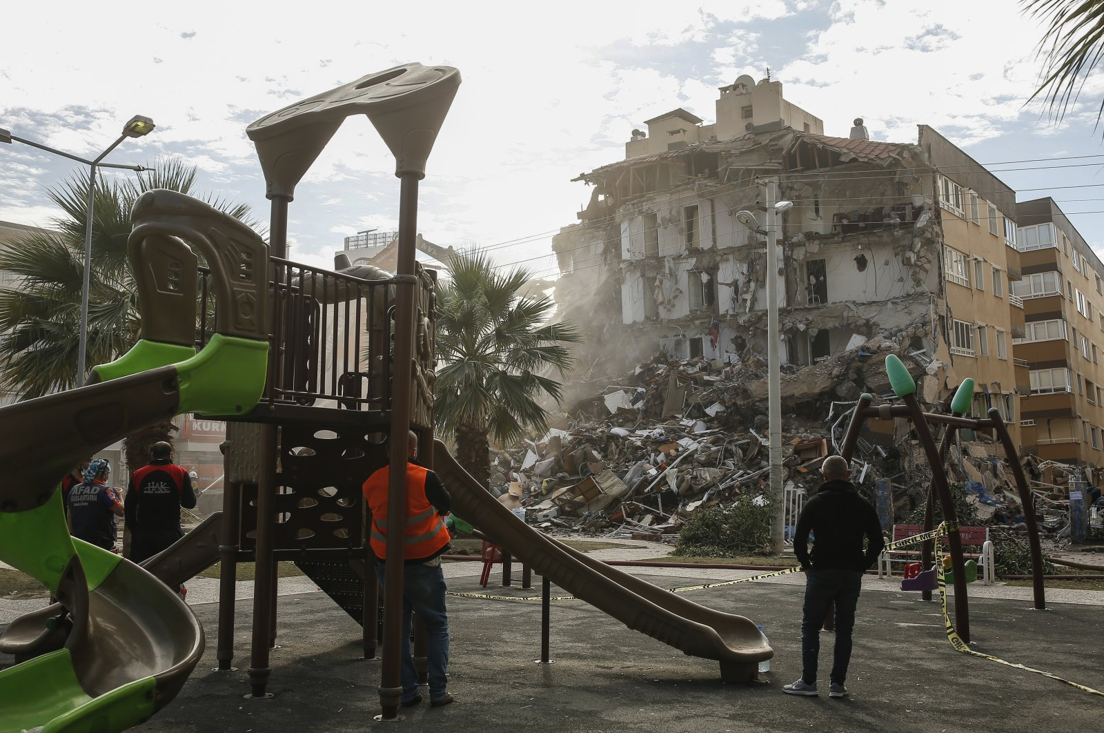 People inspect the debris of a collapsed building from a nearby playground after the earthquake in Izmir, Turkey, Nov. 2, 2020. (AP Photo)