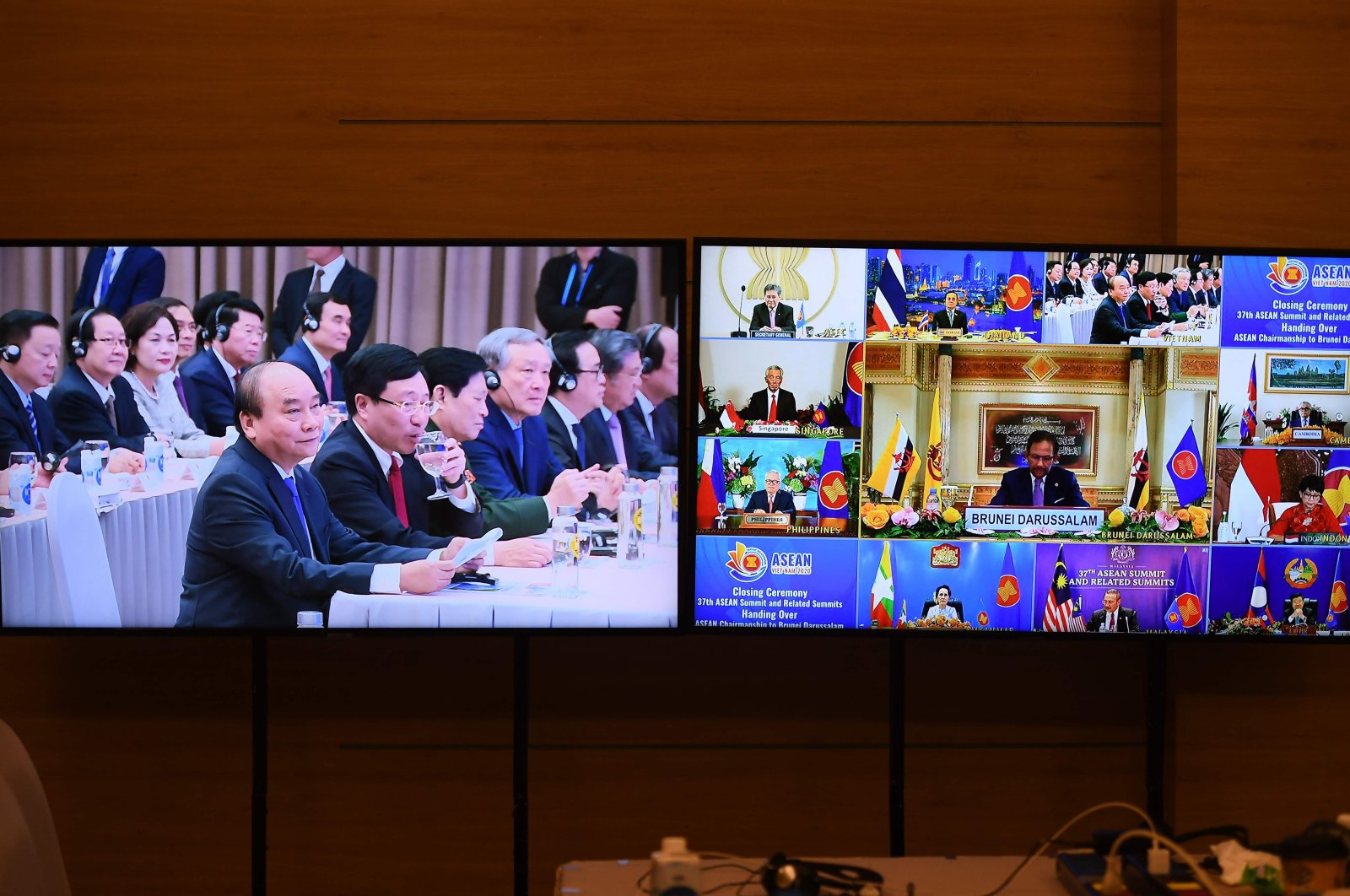 Vietnam's Prime Minister Nguyen Xuan Phuc (4th L) looks on as the next Association of Southeast Asian Nations (ASEAN) summit host Brunei's Sultan Hassanal Bolkiah (2nd R), as seen on TV monitors, addresses the ASEAN closing ceremony in Hanoi, Nov. 15, 2020. (AFP Photo)