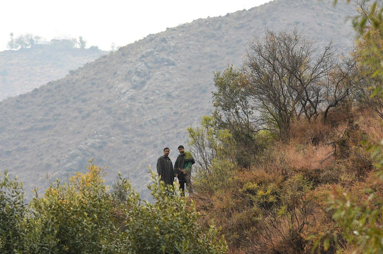 Local residents look out from the top of a hill at Kamal Kote village near the Line of Control (LOC), the de facto border between Pakistan and India, at Uri some 135 kilometers (22 miles) east of Srinagar on Nov. 14, 2020. (AFP Photo)