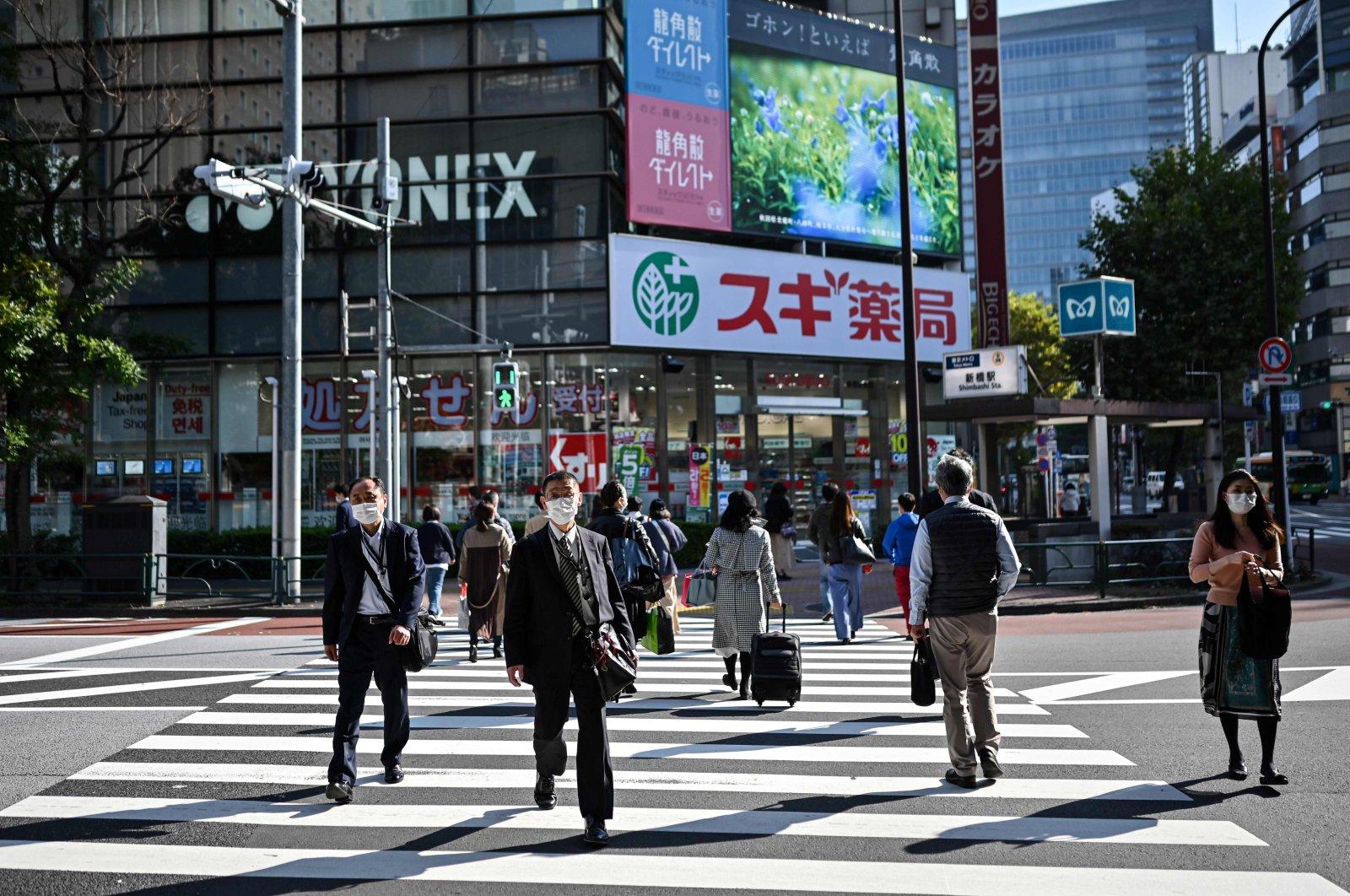 People walk on a pedestrian crossing in Tokyo, Japan, Nov. 16, 2020. (AFP Photo)