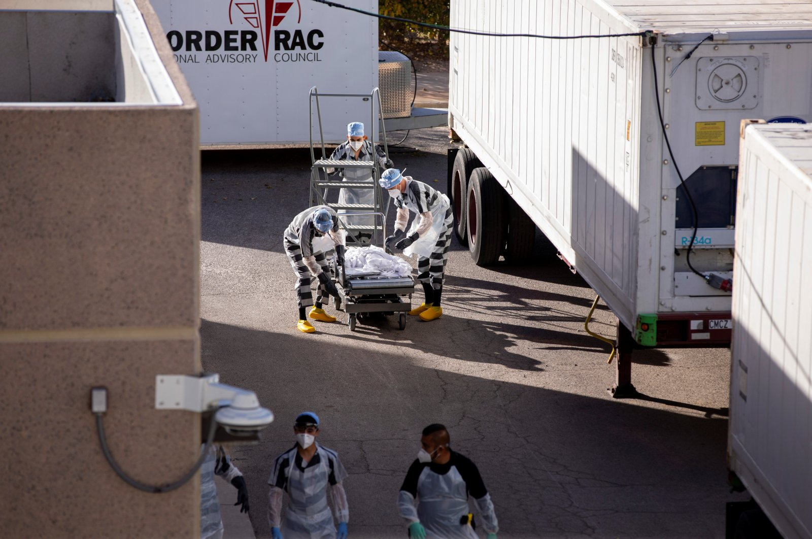 El Paso County detention inmates, also known as trustees (low-security inmates) help move bodies to refrigerated trailers deployed during a surge of COVID-19 deaths, outside the Medical Examiner's Office in El Paso, Texas, U.S. Nov. 14, 2020.  (Reuters Photo)