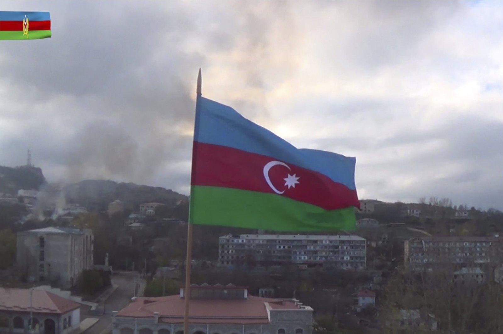 An Azerbaijani flag flies in the wind atop a building in the town of Shusha in the region of Nagorno-Karabakh, Azerbaijan, Nov. 9, 2020. (AFP Photo)