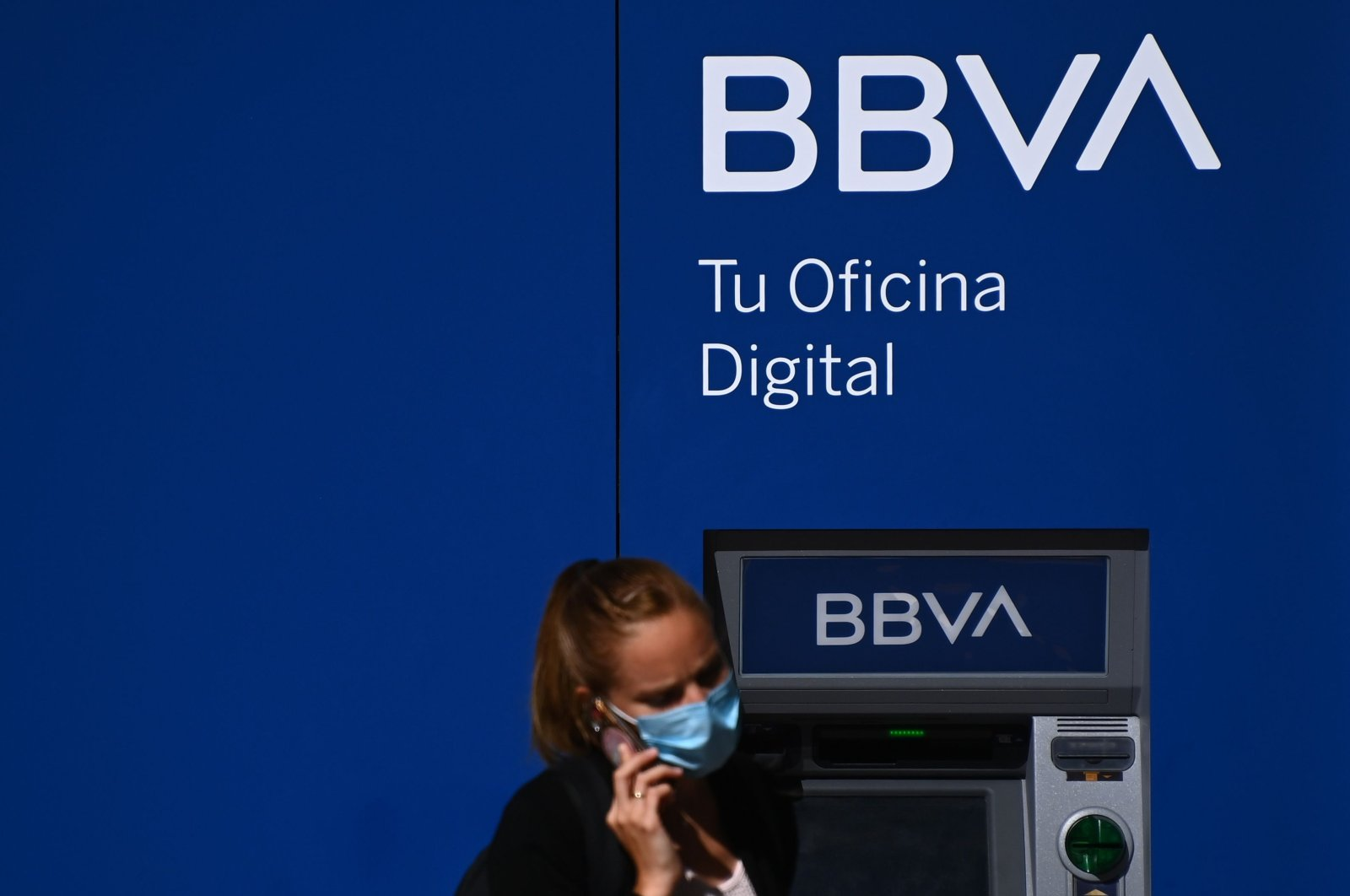 A woman uses a smartphone in front of an ATM of the BBVA in Madrid, Spain, Sept. 4, 2020. (AFP Photo)