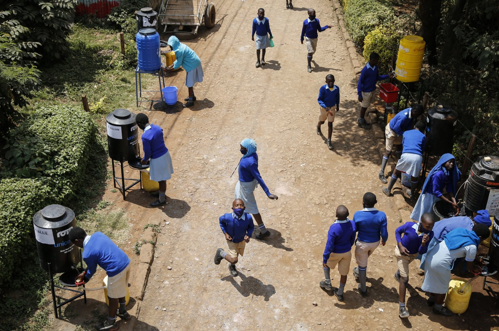 Schoolchildren sanitize their hands at washing stations as they arrive at the Olympic Primary School in Kibera, one of the capital Nairobi's poorest areas, as schools partially reopened to allow students to prepare for examinations, in Kenya, Oct. 12, 2020. (AP Photo)
