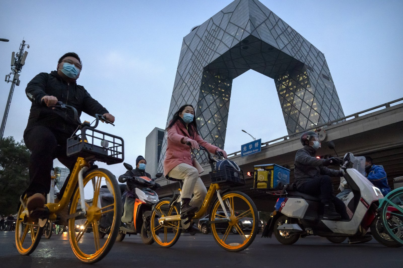 People wearing face masks to protect against the coronavirus spread ride bicycles in Beijing, China, Nov. 13, 2020. (AP Photo)