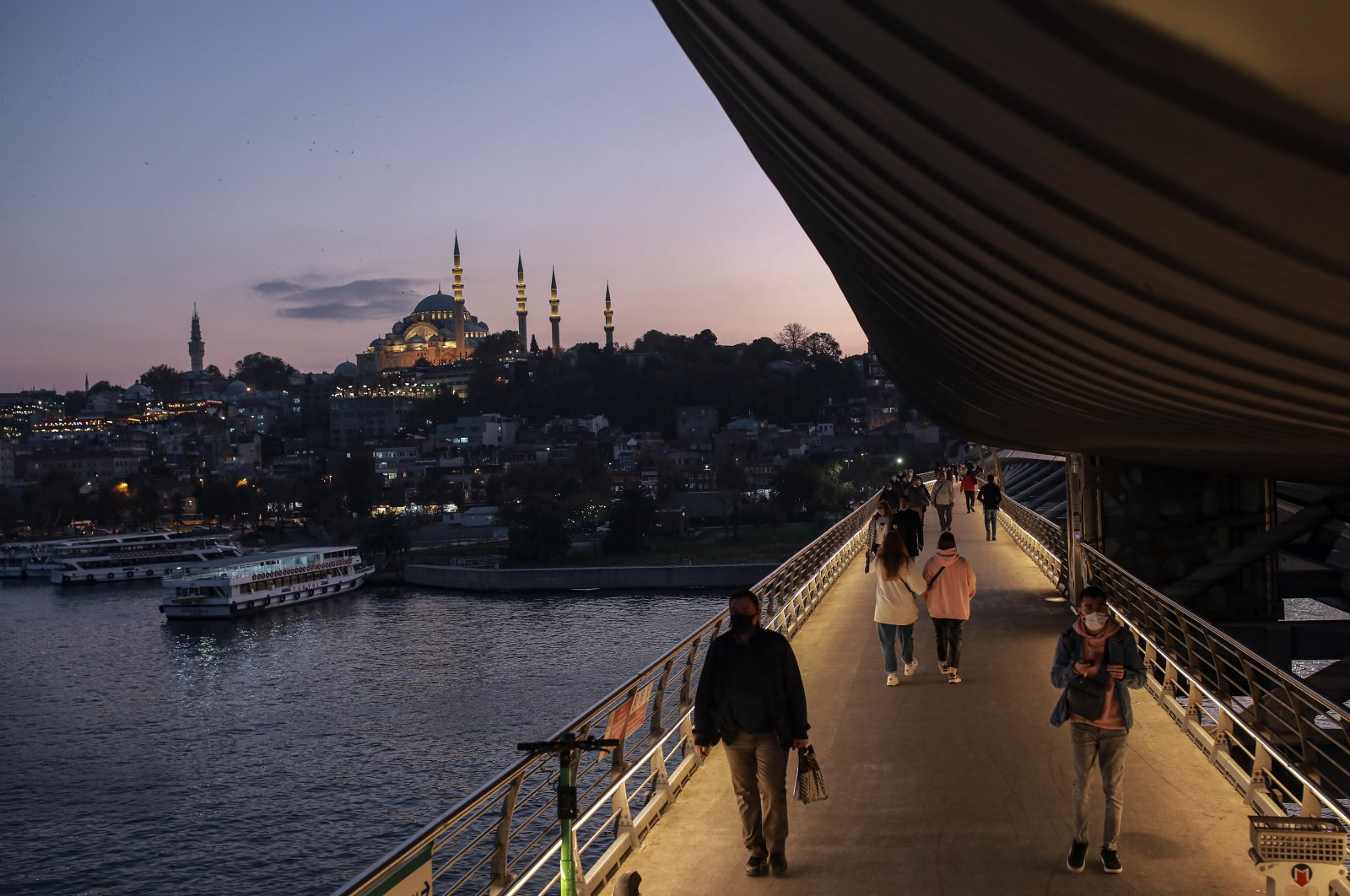 Backdropped by the Süleymaniye Mosque, people wearing protective masks to help prevent the spread of the coronavirus walk on the Golden Horn Bridge in Istanbul, Turkey, Nov. 16, 2020. (AP Photo)